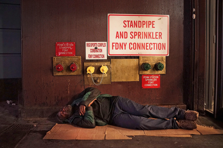 A homeless man sleeps on a Manhattan street on Aug. 22, 2014 in New York City.