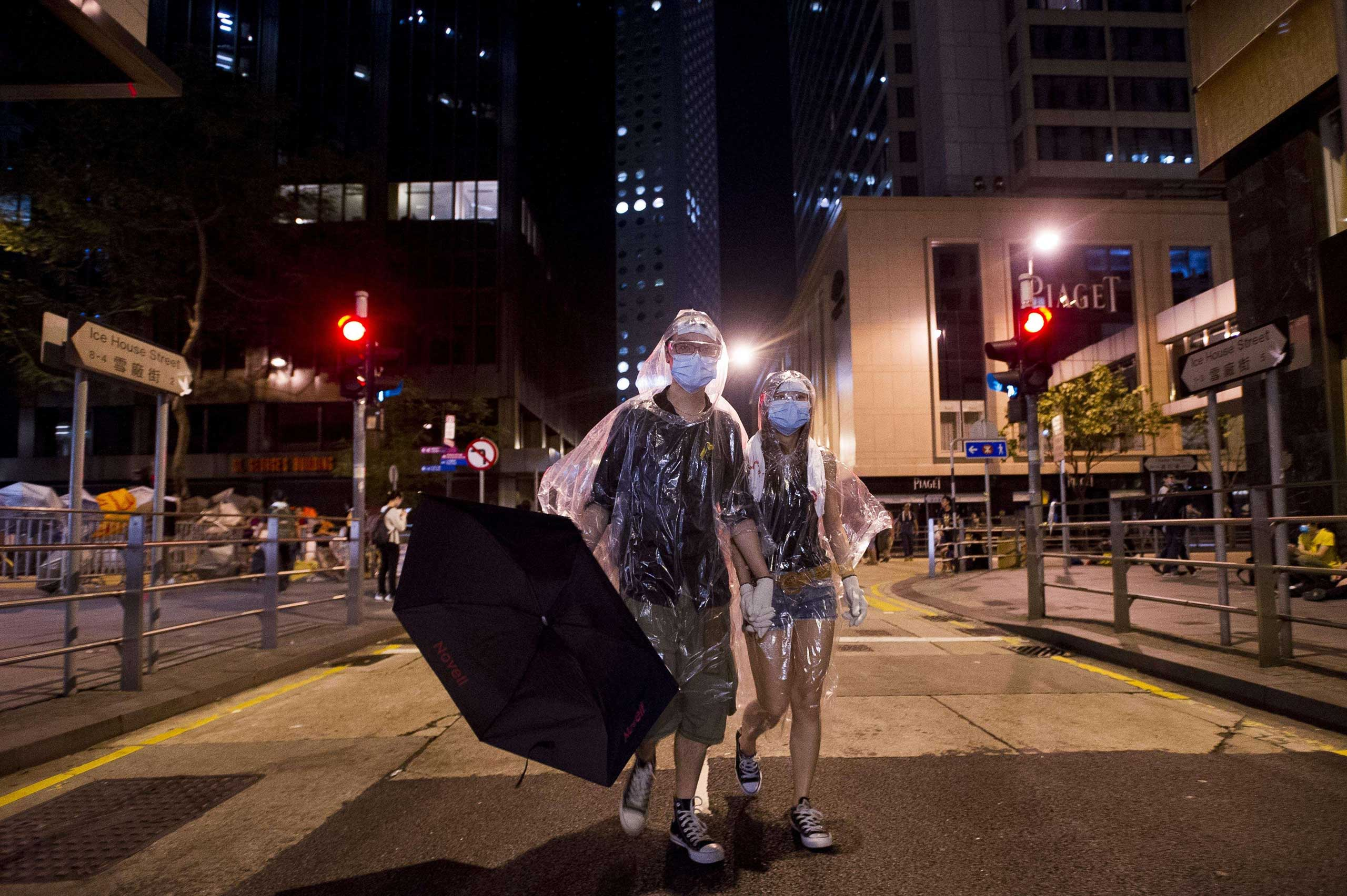 A couple wearing protective masks and ponchos walk through Admiralty district as part of pro-democracy protests in Hong Kong on Sept. 30, 2014.