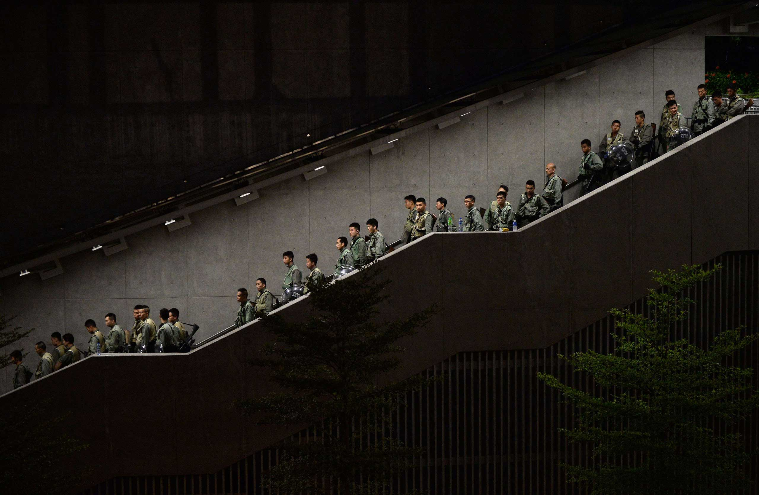Police walk down a stairwell as pro-democracy demonstrators gather for a rally outside the Hong Kong government headquarters on Sept. 29, 2014.