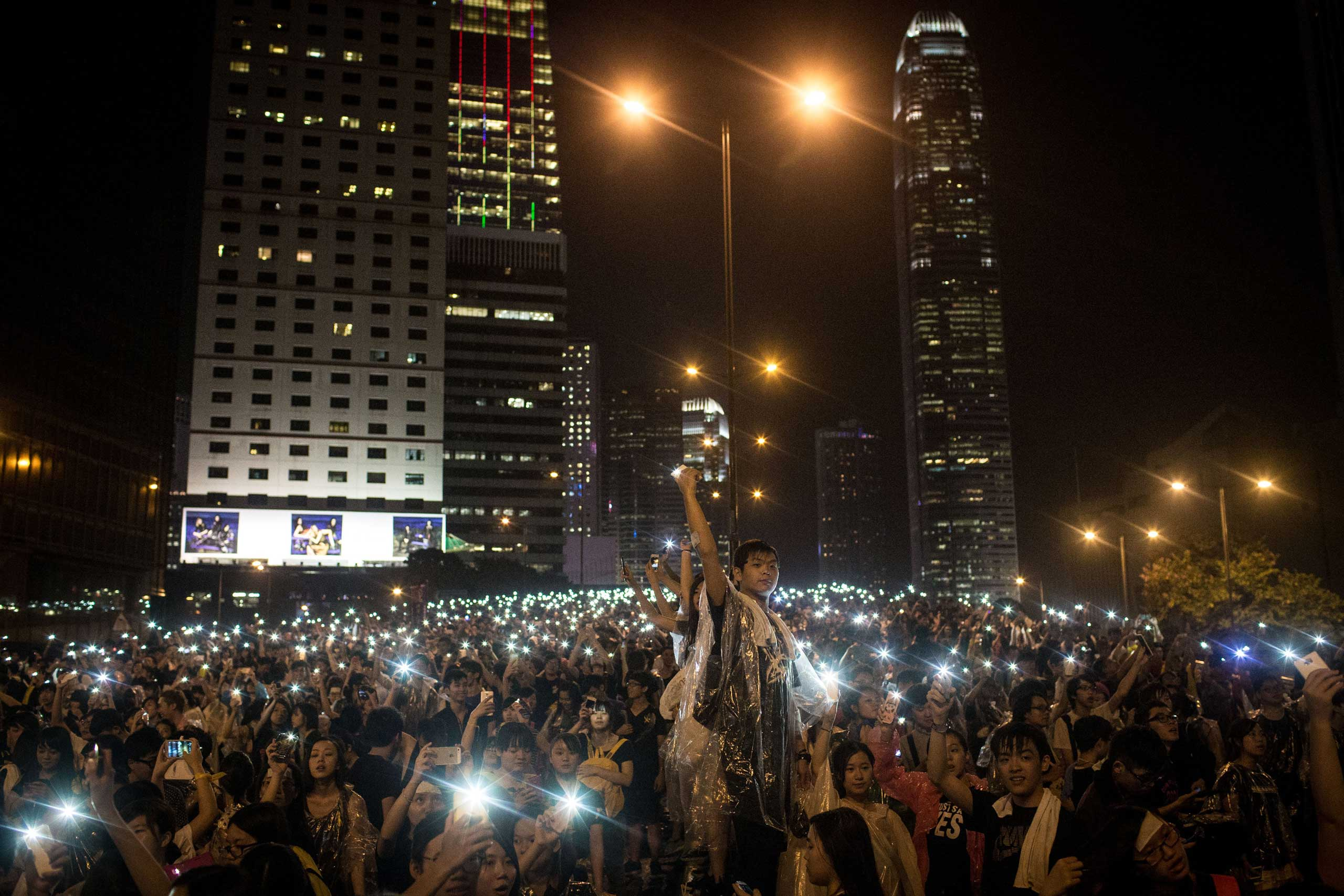Protesters sing songs and wave their cell phones in the air after a massive thunderstorm passed over outside the Hong Kong Government Complex on Sept. 30, 2014 in Hong Kong, Hong Kong.