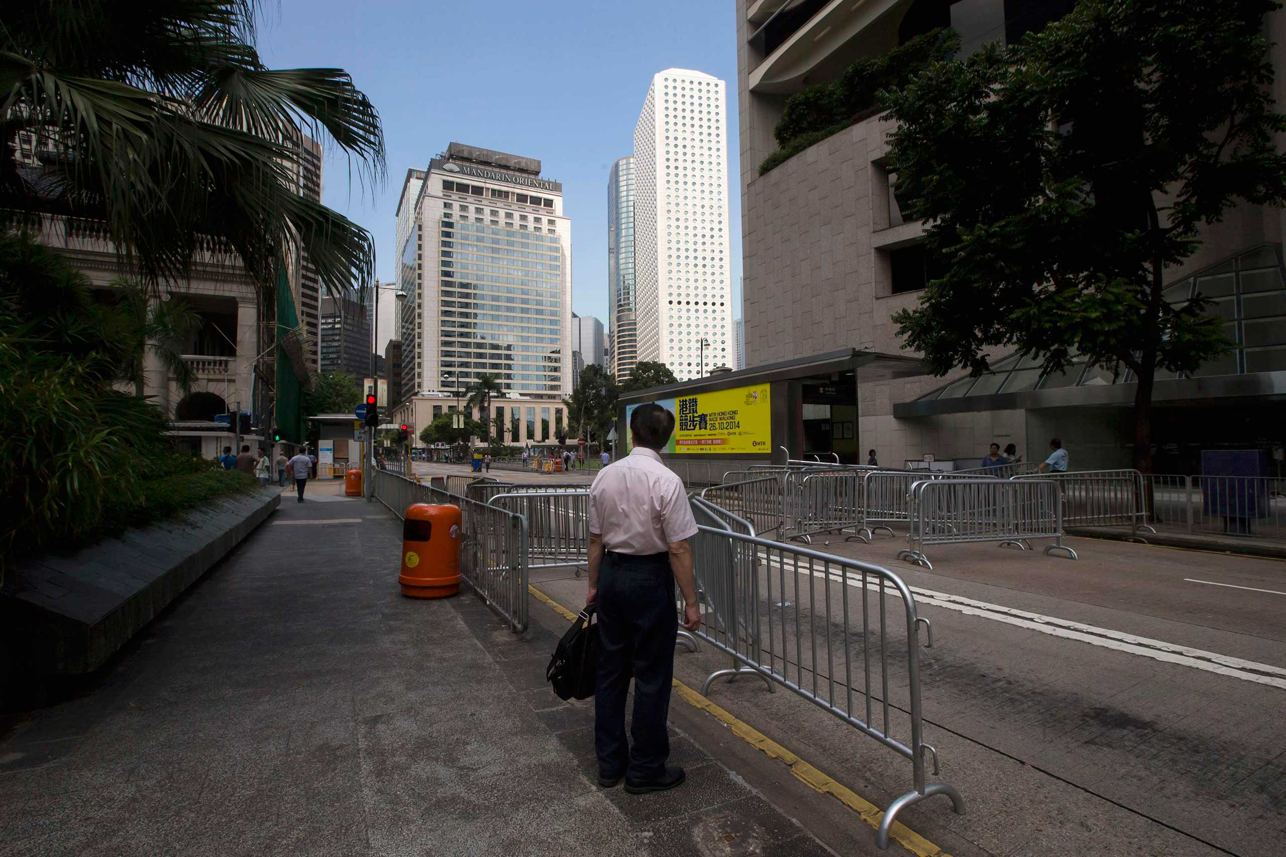 A businessman stands in front of a road block set up by protesters at the main street of the financial Central district in Hong Kong Sept. 29, 2014.