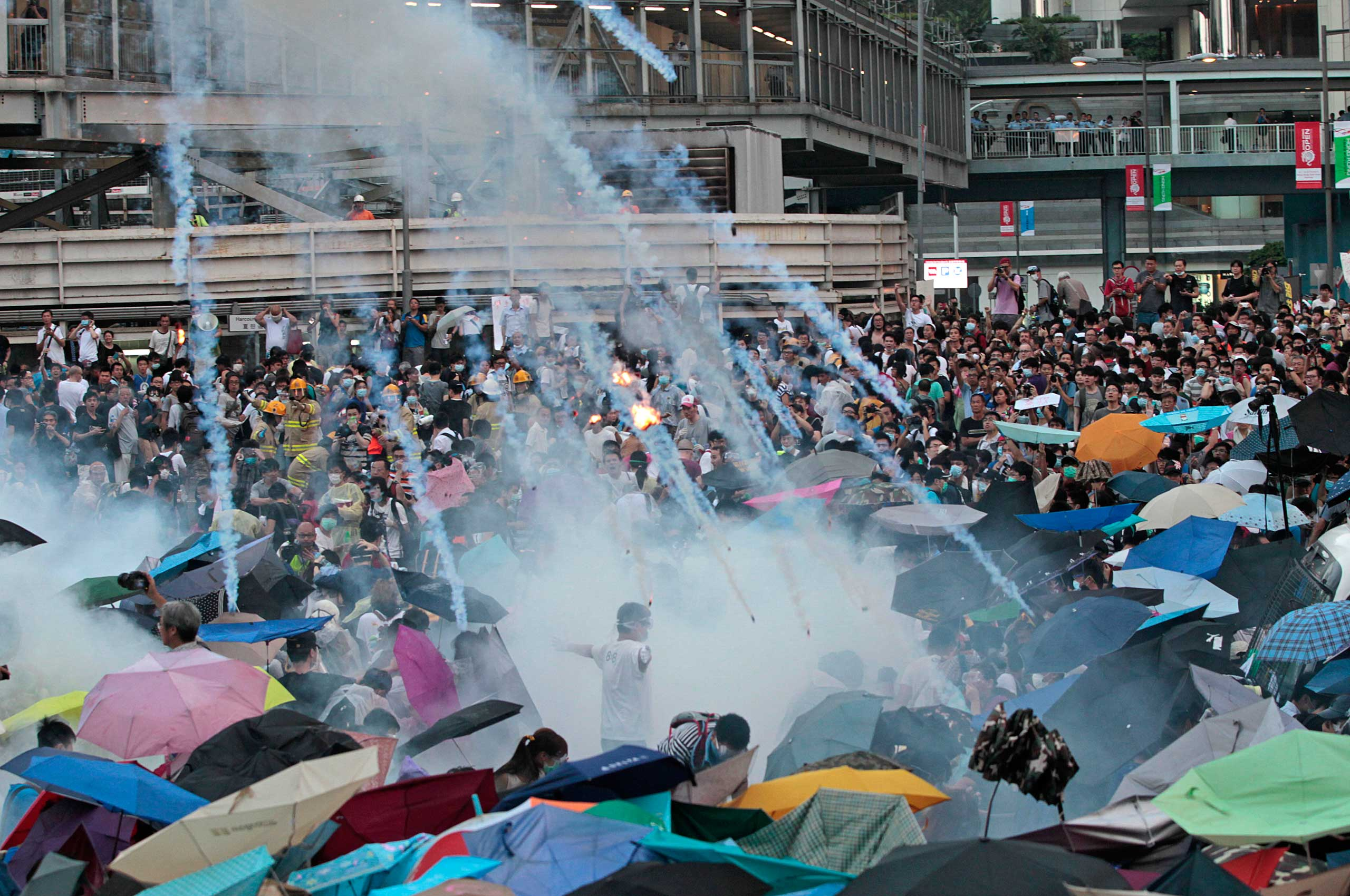 Riot police launch tear gas into the crowd as thousands of protesters surround the government headquarters in Hong Kong, Sept. 28, 2014.