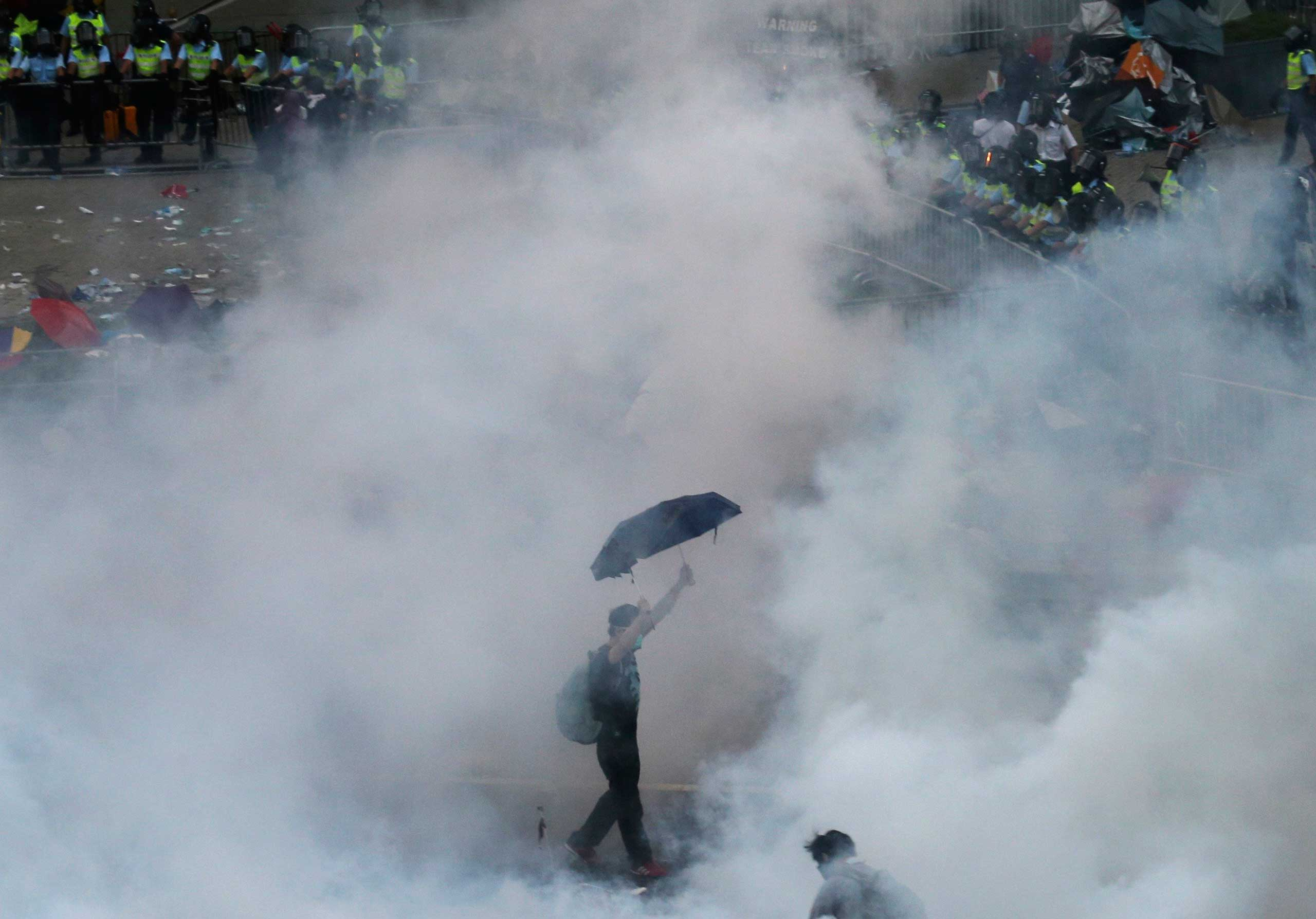 A protester walks in tear gas fired by riot policemen after thousands of protesters blocking the main street to the financial Central district outside the government headquarters in Hong Kong, Sept. 28, 2014.