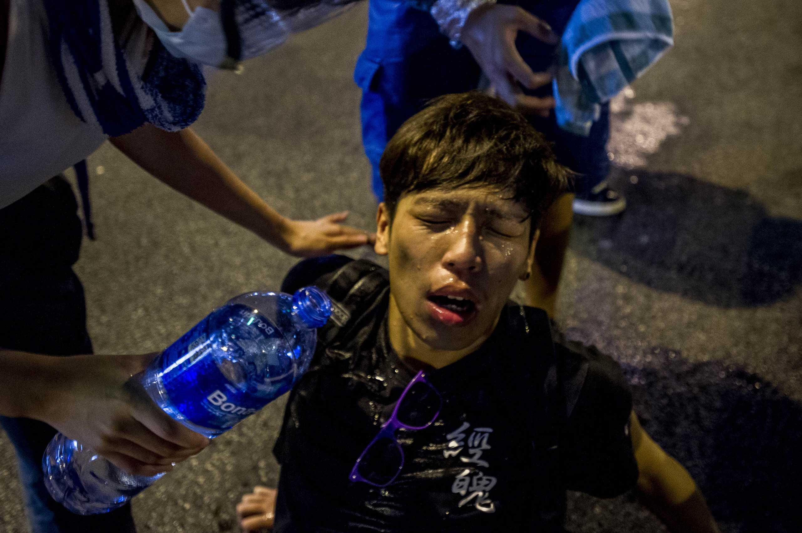 A pro-democracy demonstrator pours water over a man's face after police fired tear gas at protesters during a rally near the Hong Kong government headquarters on Sept. 28, 2014.