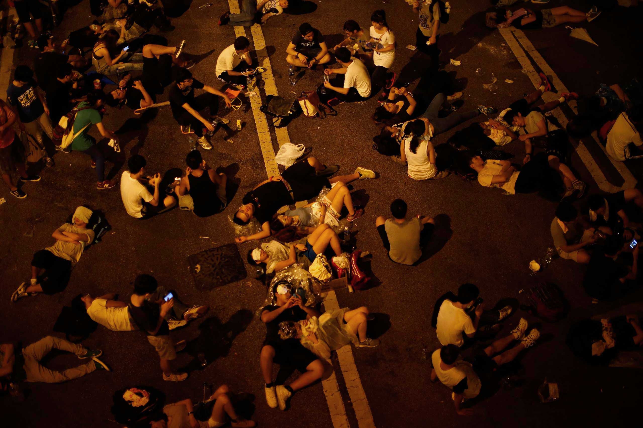 Some of the protesters sleep as they block the main street to the financial Central district outside the government headquarters, in Hong Kong, Sept, 29, 2014.