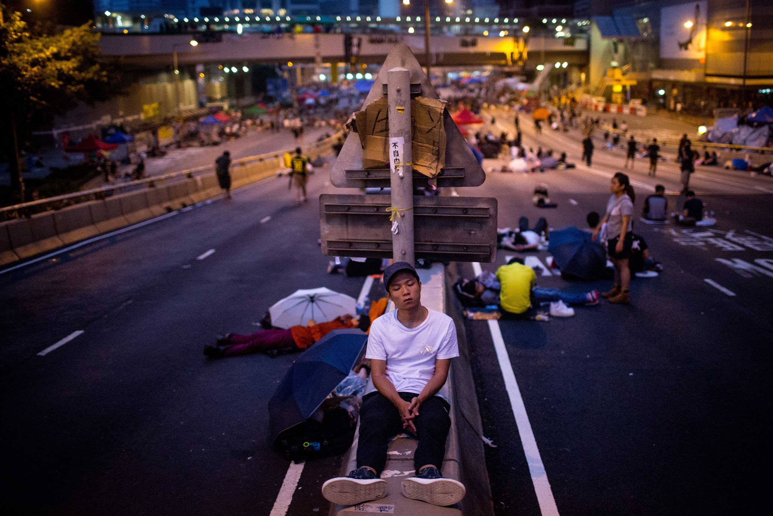 A pro-democracy protester sleeps on a concrete road divider on a street outside the Hong Kong Government Complex on Oct. 5, 2014 in Hong Kong.
