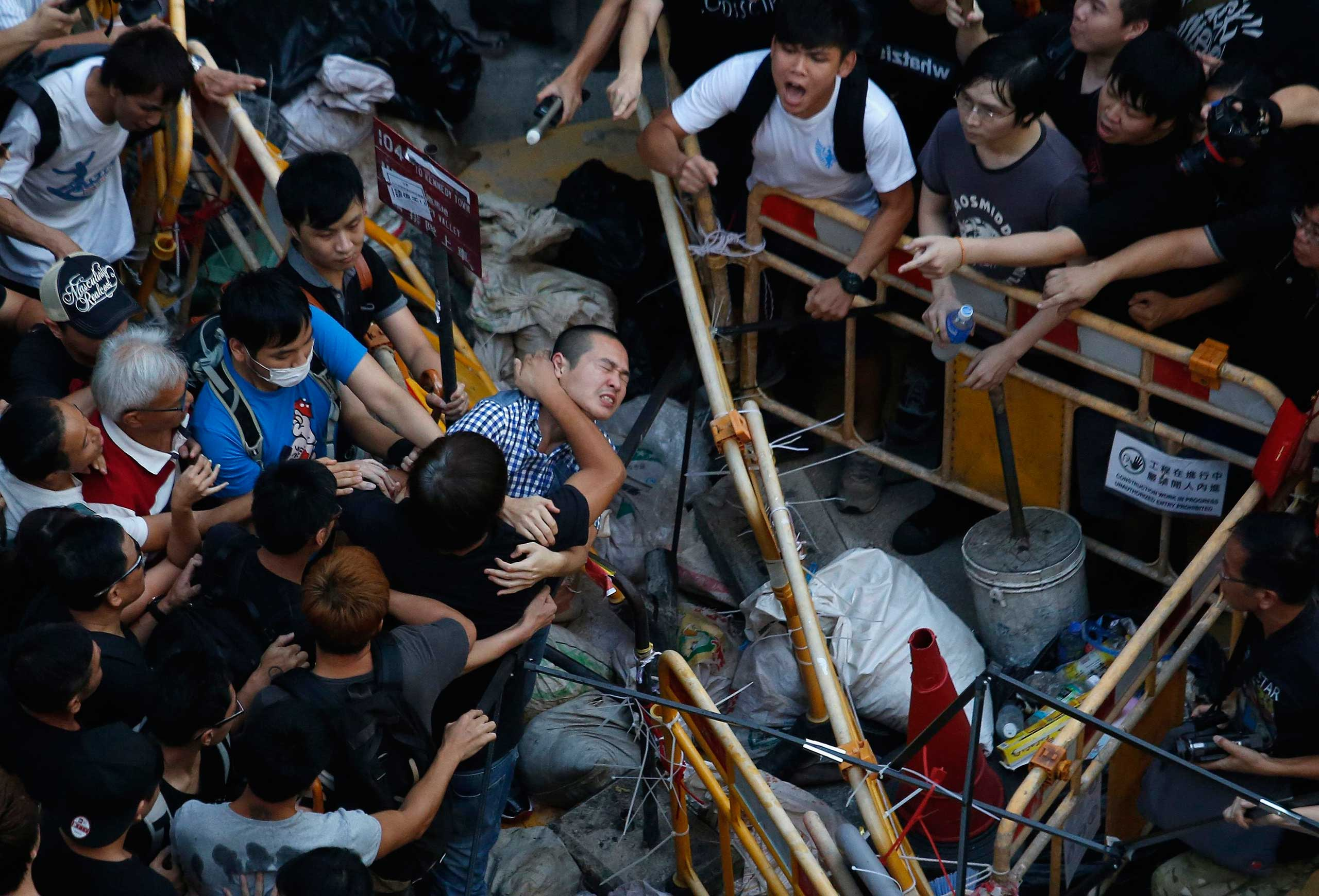 People try to prevent a man from removing a barricade set up by pro-democracy protesters blocking a main road at Hong Kong's shopping Mongkok district Oct. 4, 2014.
