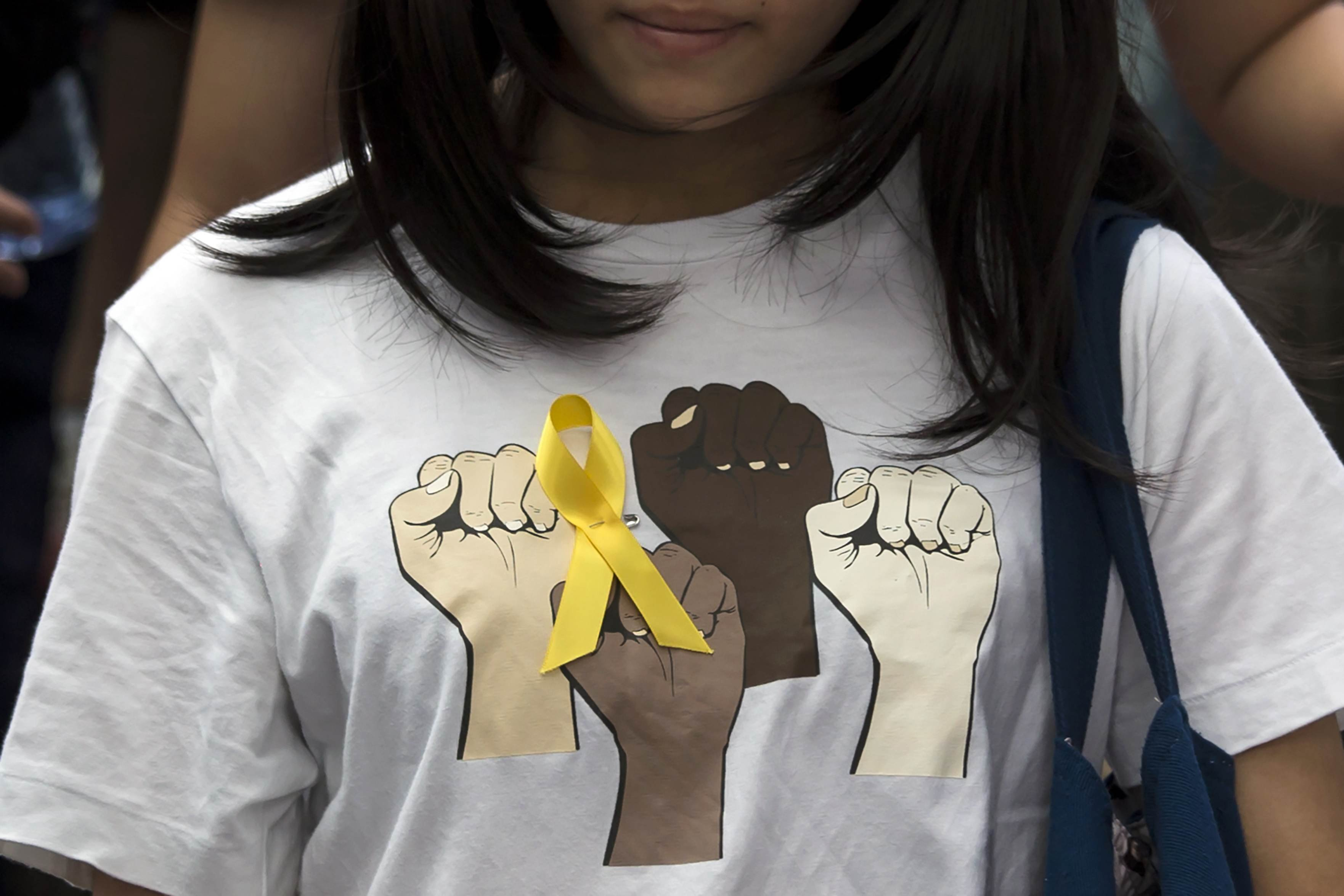 A secondary school student wears a yellow ribbon pinned to her T-shirt during a rally against Beijing's election framework for Hong Kong, outside the government headquarters in Hong Kong on Sept. 26, 2014.