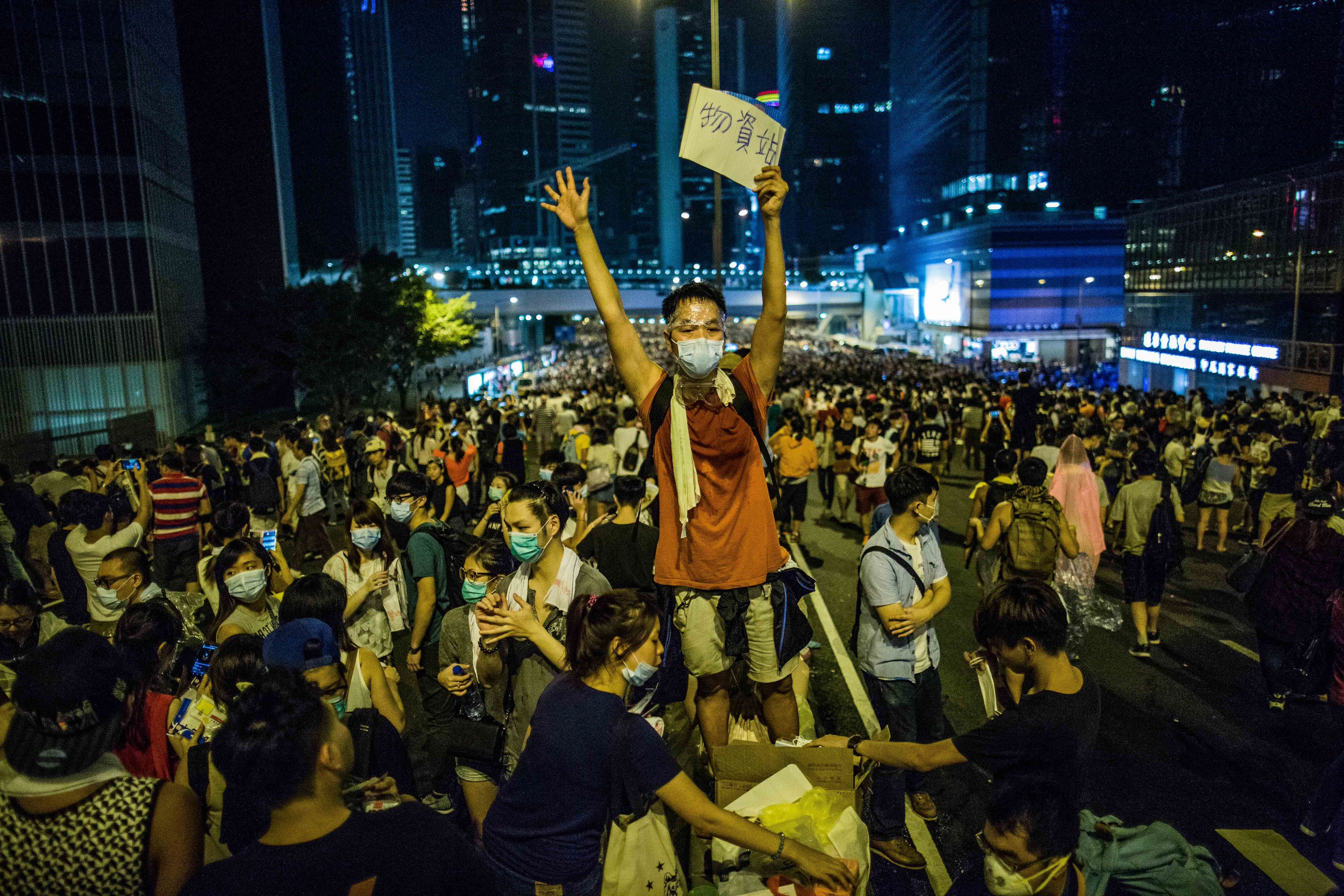 A man holds a sign that reads  Supplies  in Hong Kong on Sept. 28, 2014. The pro-democracy protesters occupy several city blocks surrounding the government headquarters, effectively blocking key roads linking Central to the rest of Hong Kong Island