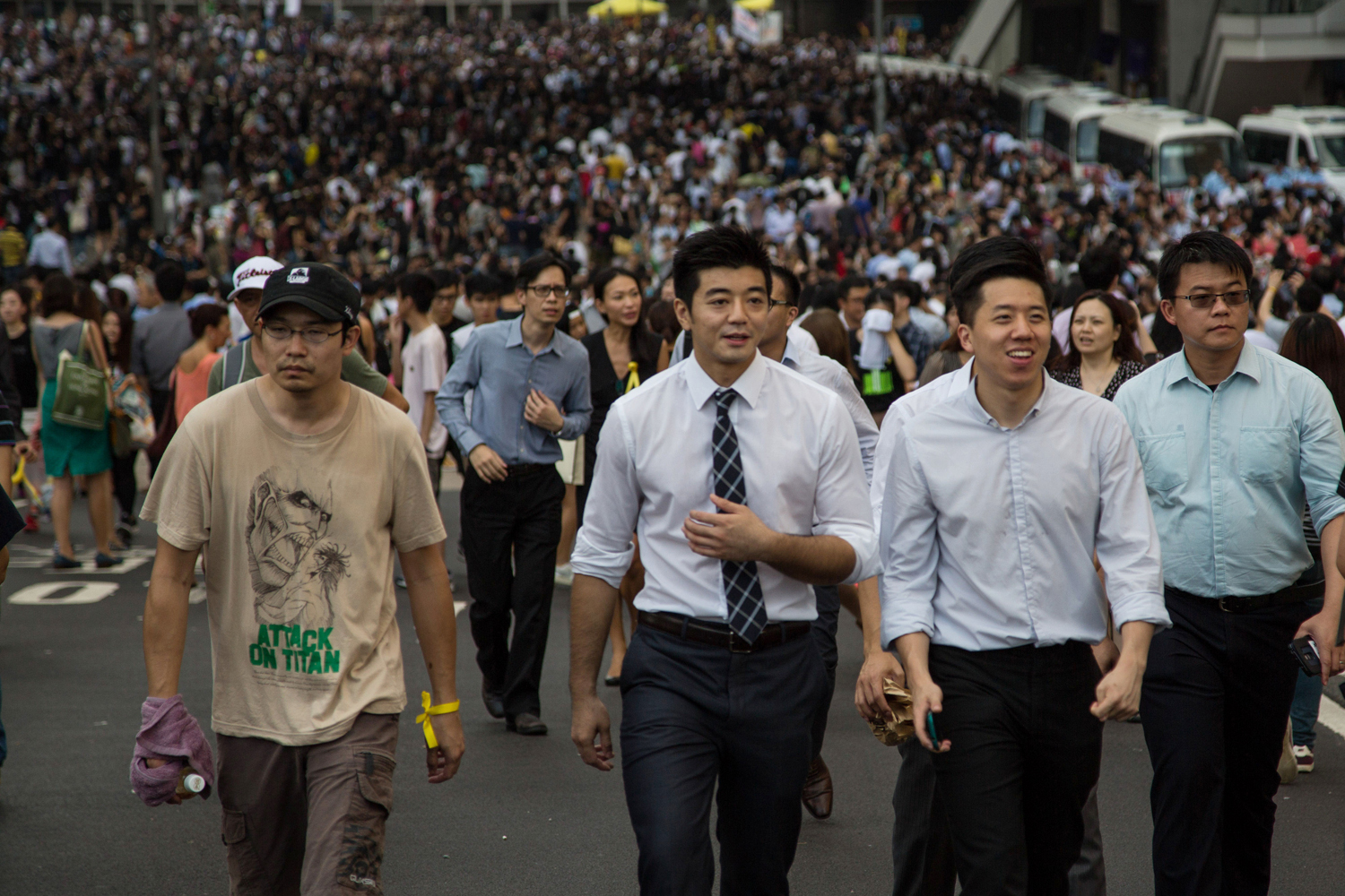 Office workers walk through closed off streets in front of protesters near the central government offices in the business district of Central in Hong Kong on Sept. 29, 2014