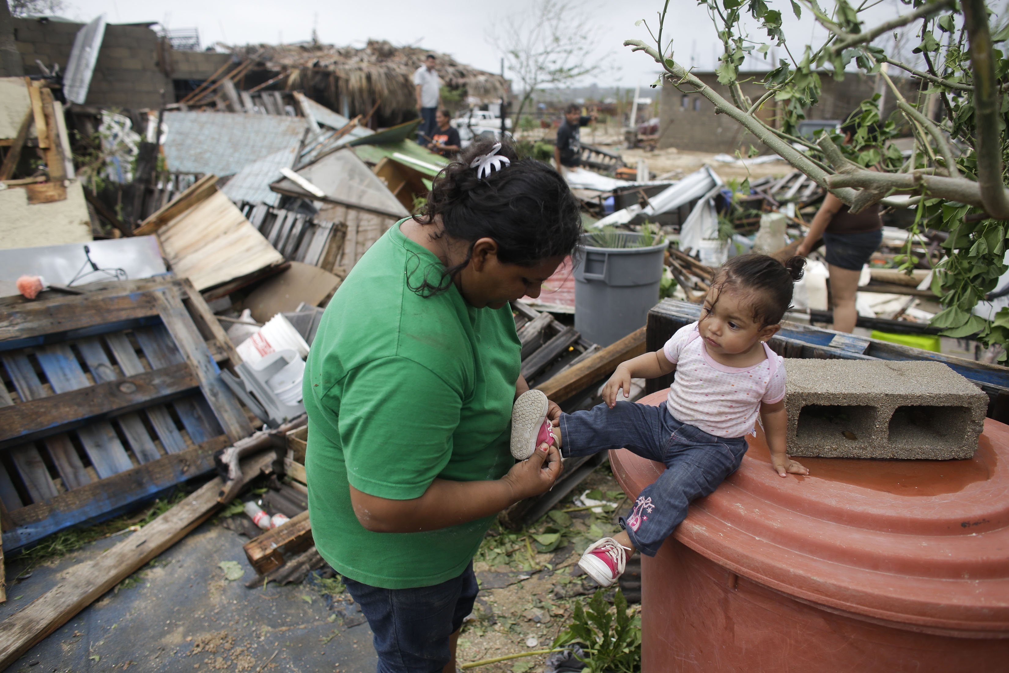 Maria Ramirez, left, puts the shoes on her one-year-old niece Maritza next to the remains of their home that was destroyed by Hurricane Odile in Los Cabos, Mexico,  Sept. 15, 2014.