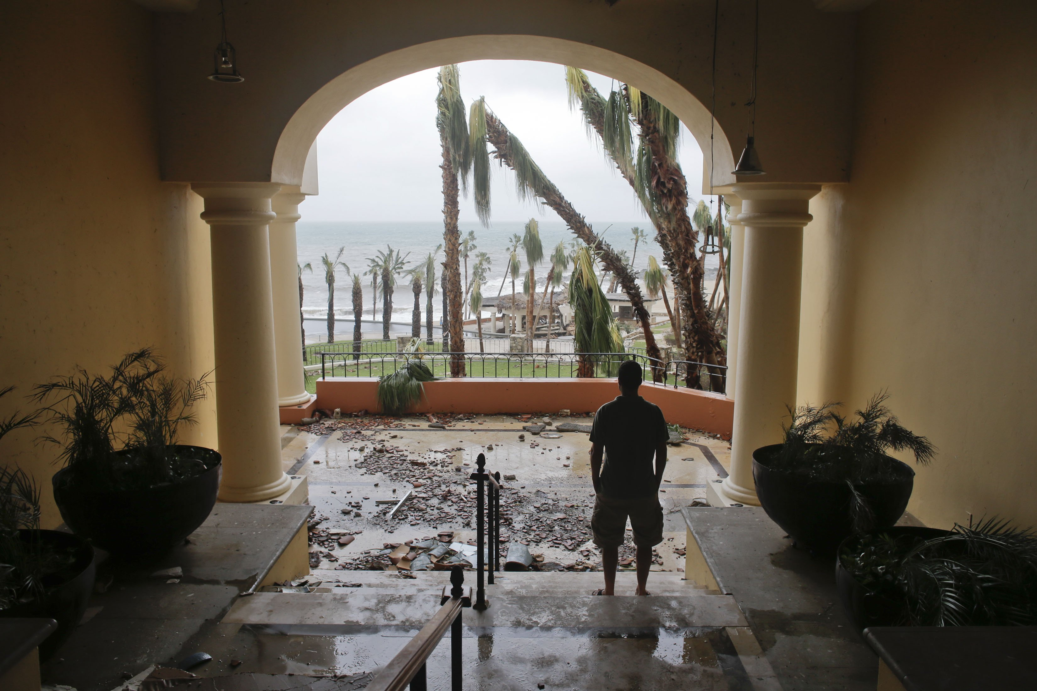 A tourist looks to the ocean from inside a debris-filled area at the Hilton hotel after the resort sustained severe damage from Hurricane Odile in Los Cabos, Mexico,  Sept. 15, 2014.