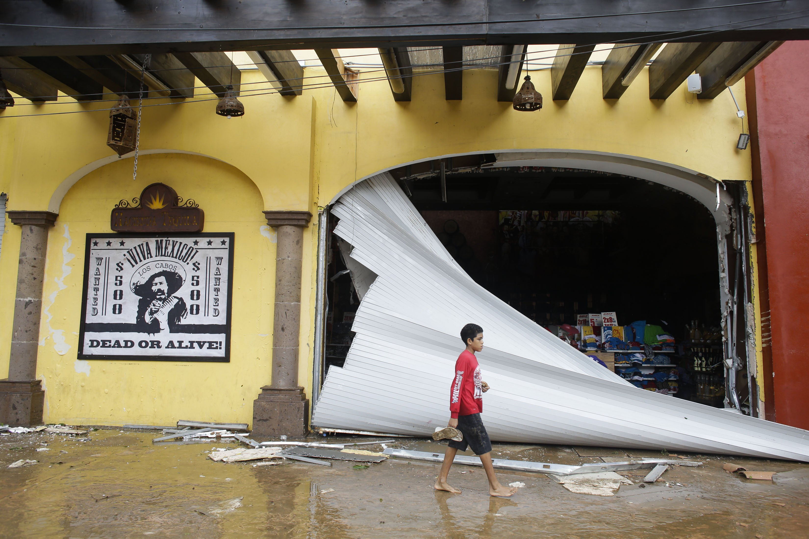 A boy walks by a souvenir store damaged by Hurricane Odile on San Lucas' main street, in Los Cabos, Mexico, Sept. 15, 2014.
