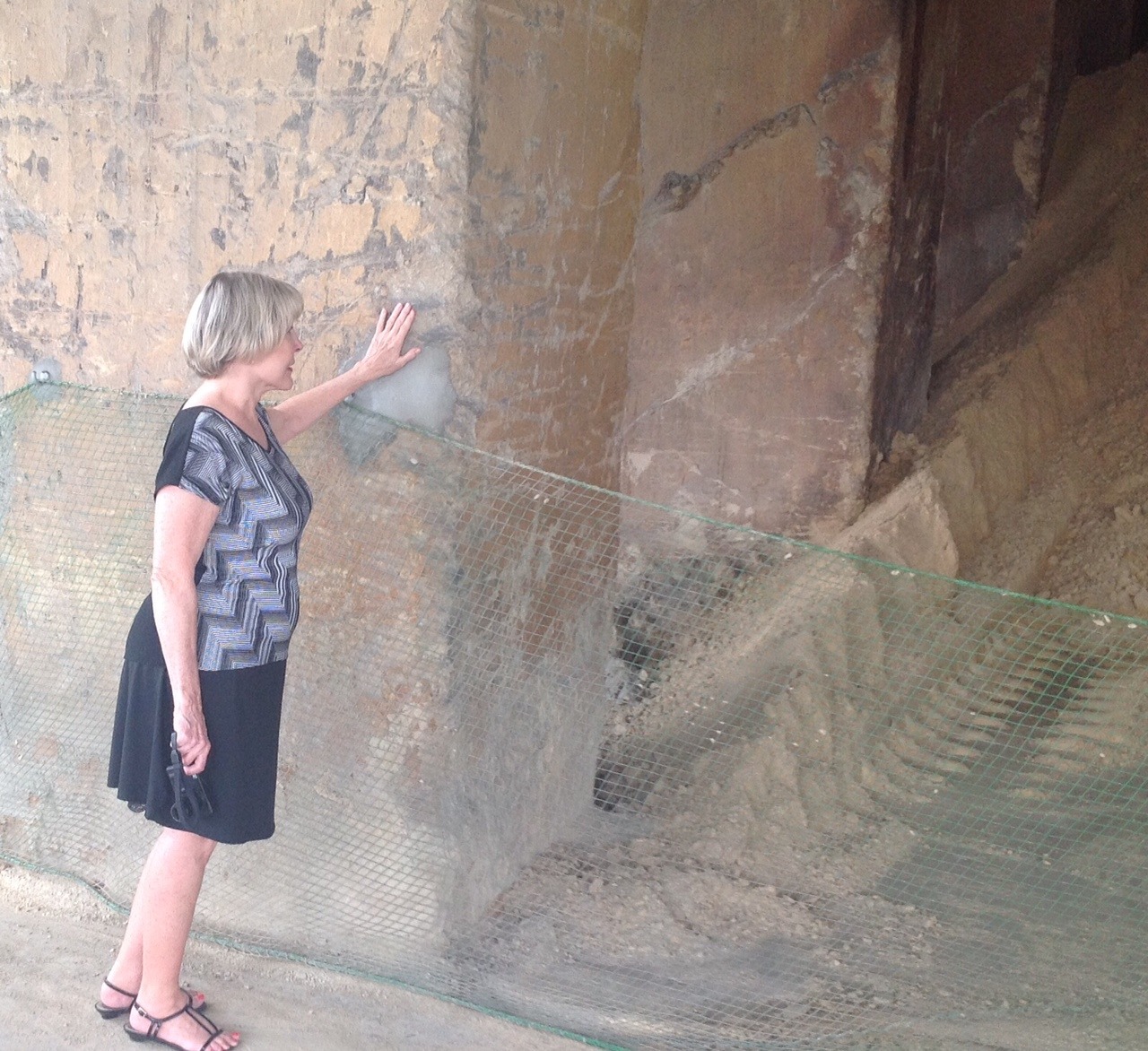 Kathy Holcomb touching the wall of one of the original buildings at the Ishihara Sangyo plant where her father labored as a POW in World War II