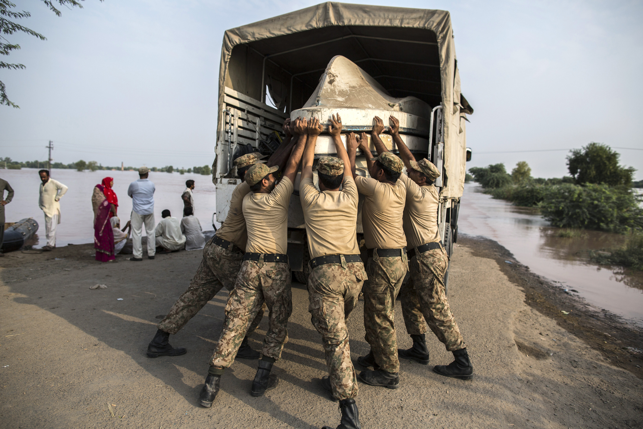 Army soldiers unload boats to be used for evacuating flood victims from their flooded houses following heavy rain in Jhang, Punjab province, Pakistan, Sept. 10, 2014.