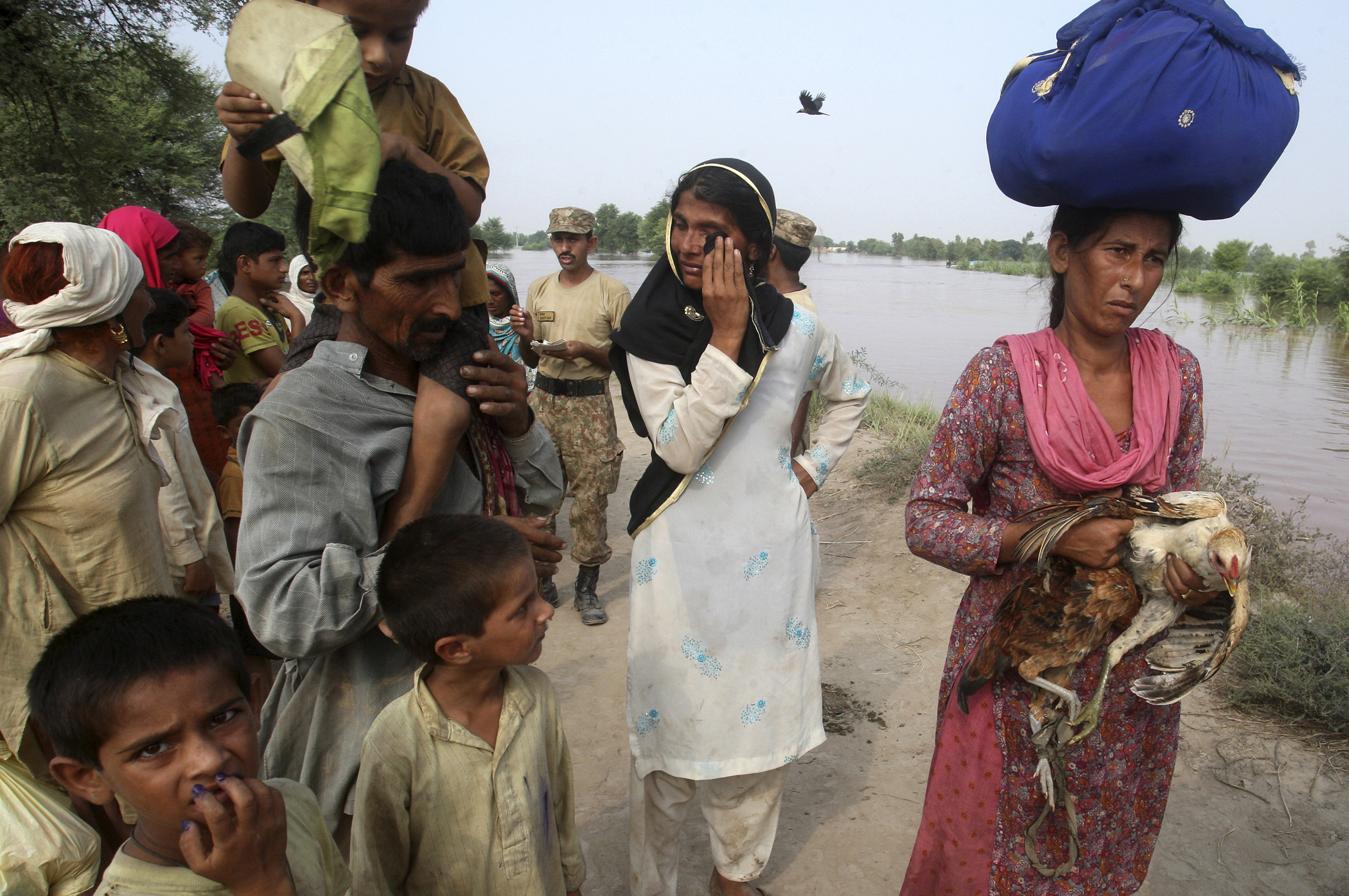 Pakistani villagers wait for boats to evacuate flooded areas along the Chenab River, in Jhang, Pakistan, Sept. 10, 2014.