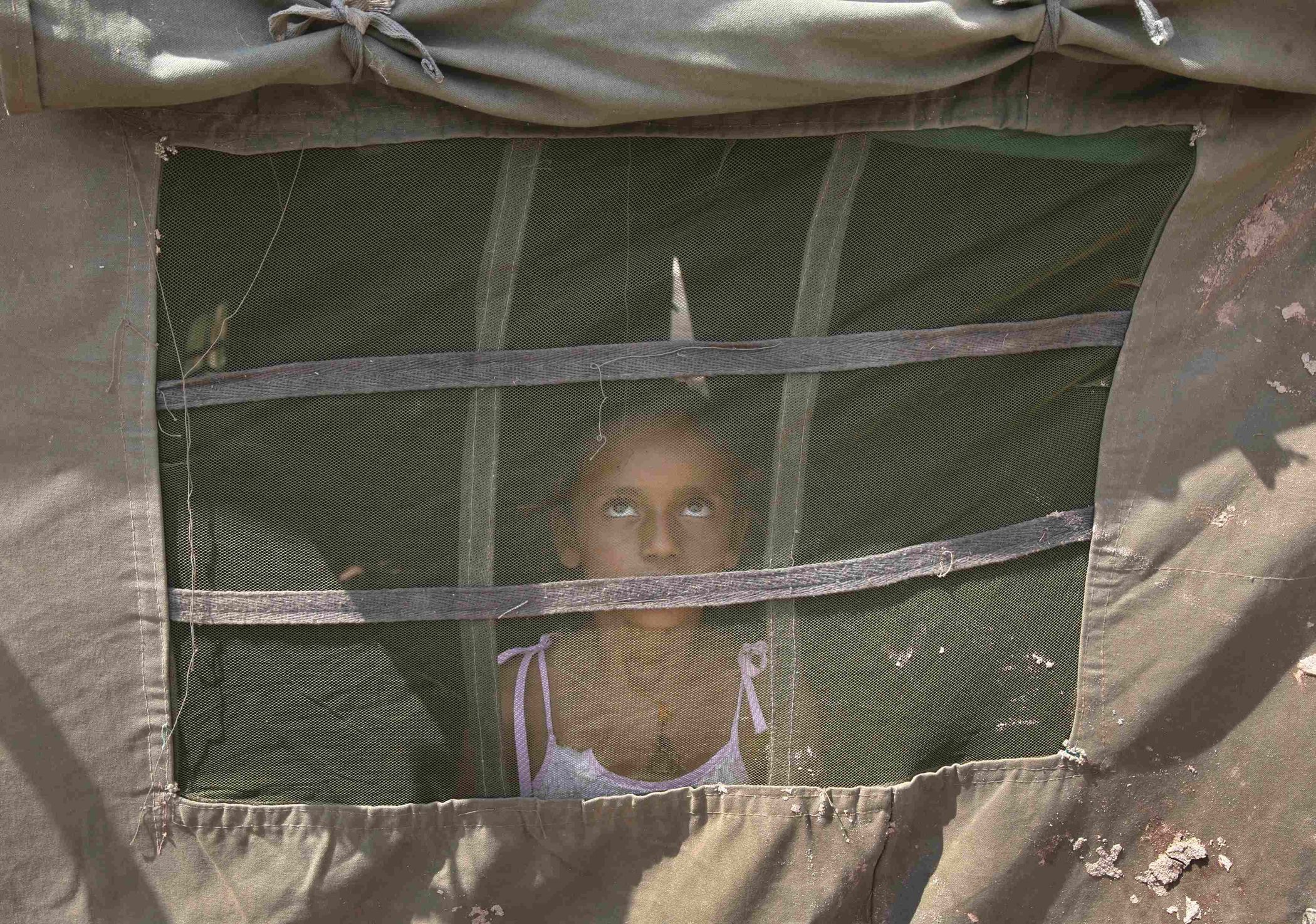 A girl from a flood-affected area watches a military chopper (not pictured) from inside an Indian Army tent at a relief camp on the outskirts of Jammu, Sept. 10, 2014.