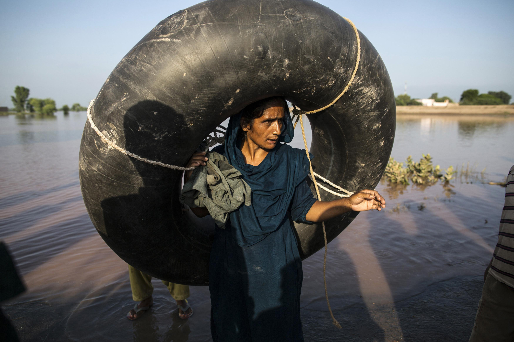 A Pakistani woman carries a rubber ring as she stands beside a flooded field following heavy rain in Cheniot, Punjab Province, Sept. 9, 2014.