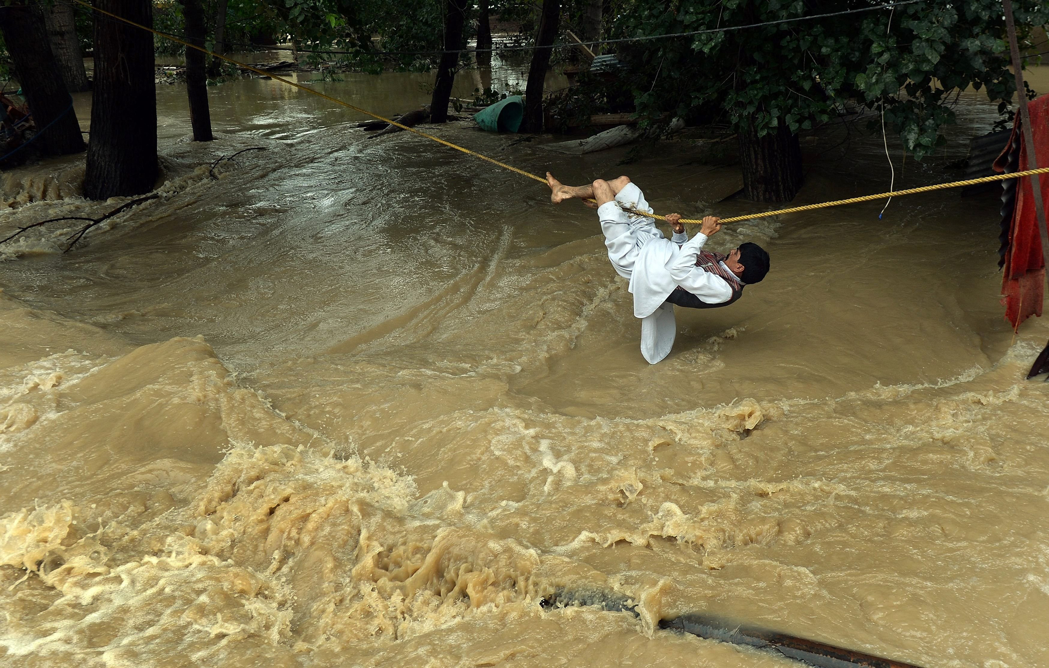 An Indian Kashmiri man crosses over flood waters with the use of a rope in Srinagar on Sept. 9, 2014.