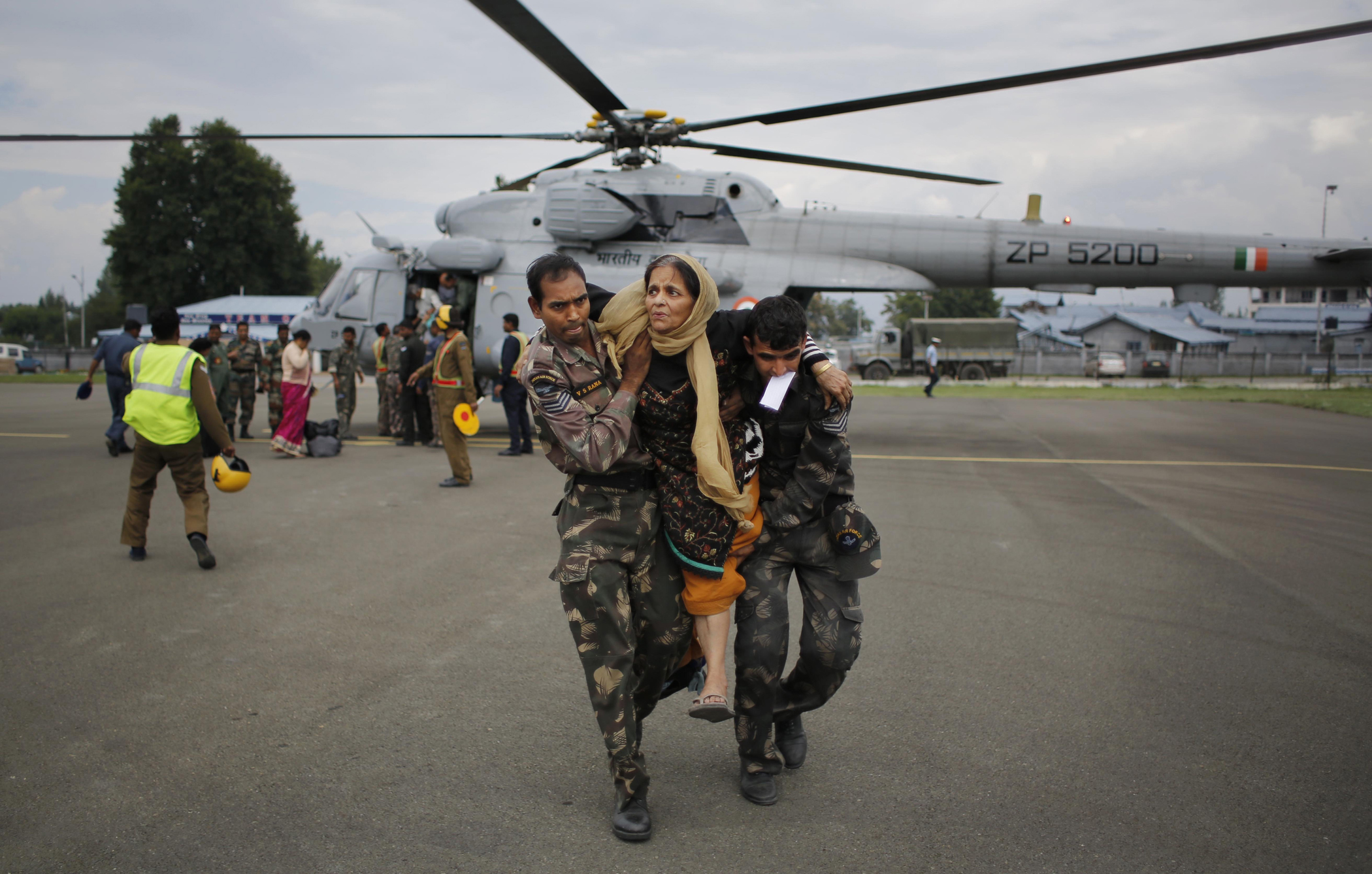 Indian soldiers carry a rescued flood victim at the Air Force Station in Srinagar, India, Sept. 9, 2014.