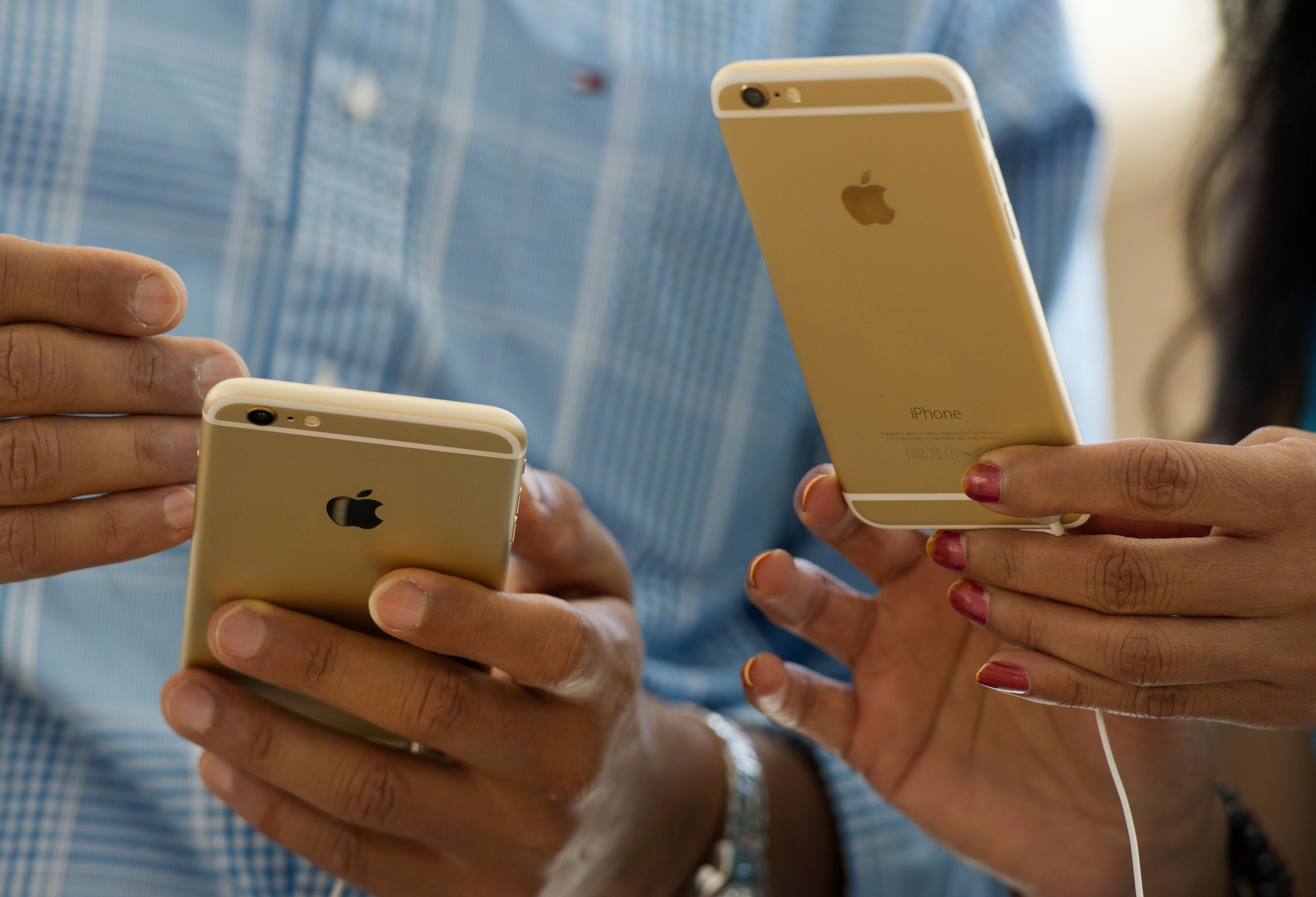 Customers compare an Apple Inc. iPhone 6, left, and iPhone 6 plus during the sales launch at an Apple store in Palo Alto, California, U.S., on Friday, Sept. 19, 2014.