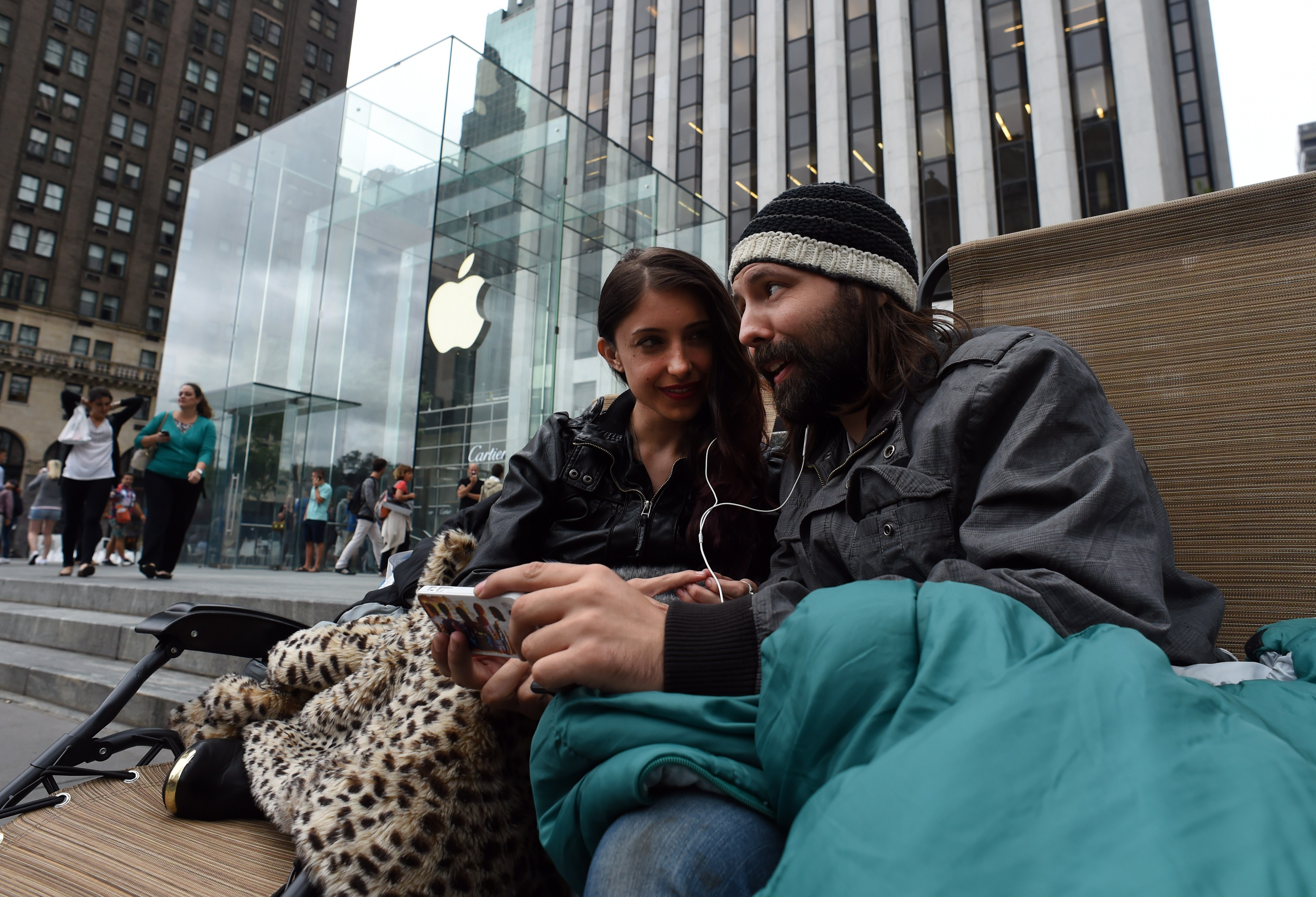 Moon Ray (L) and her husband Jason Ray talk on Skype as they wait in line September 9, 2014 outside the Apple Store on 5th Avenue in New York.