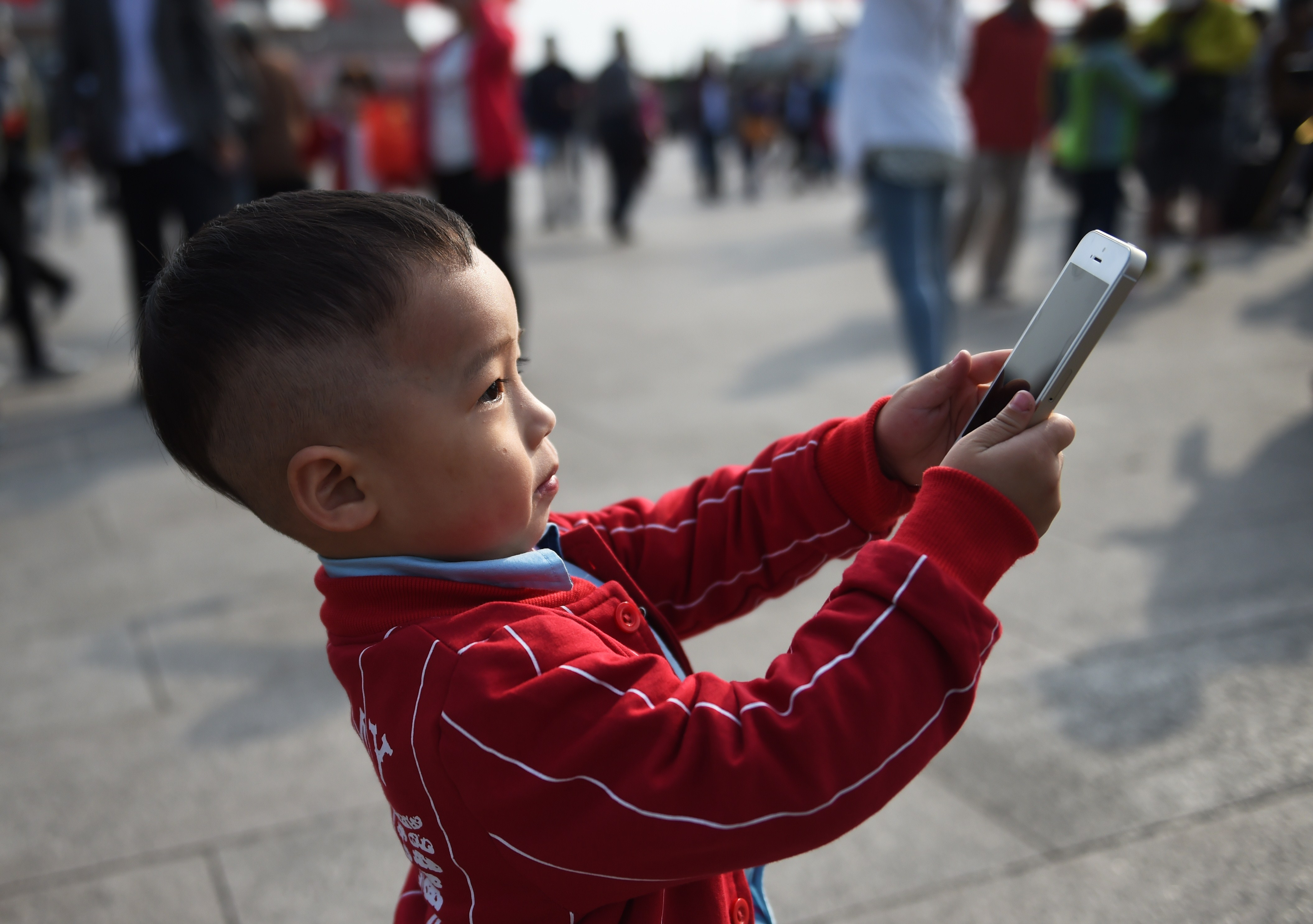 A young boy uses an iPhone to take photos in Tiananmen Square in Beijing on September 30, 2014.