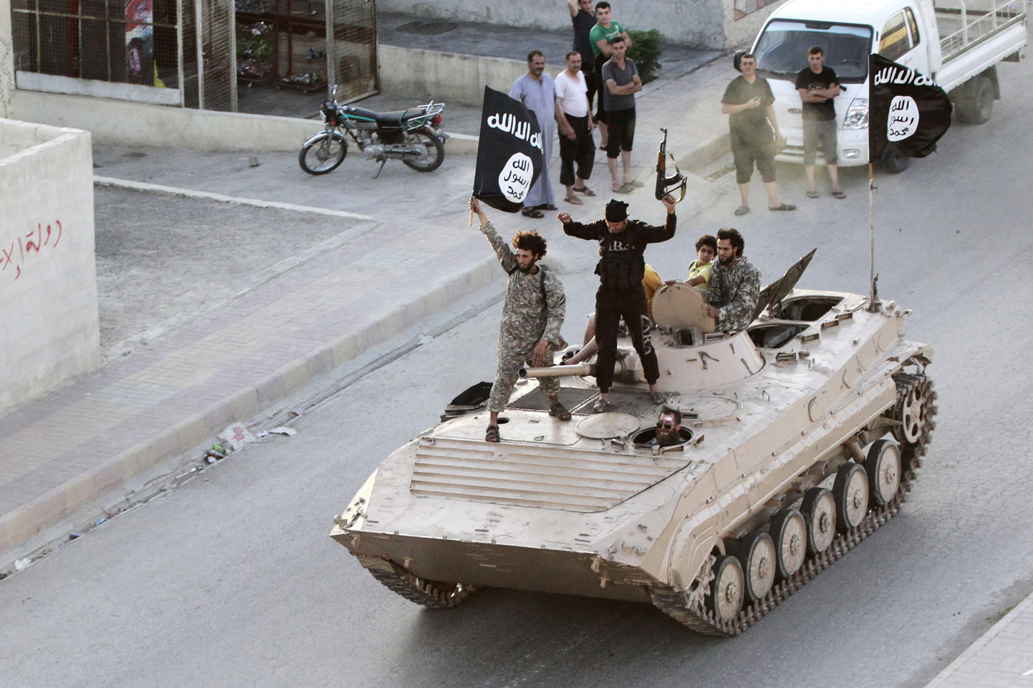 Militant Islamist fighters take part in a military parade along the streets of northern Raqqa province in Syria, June 30, 2014.