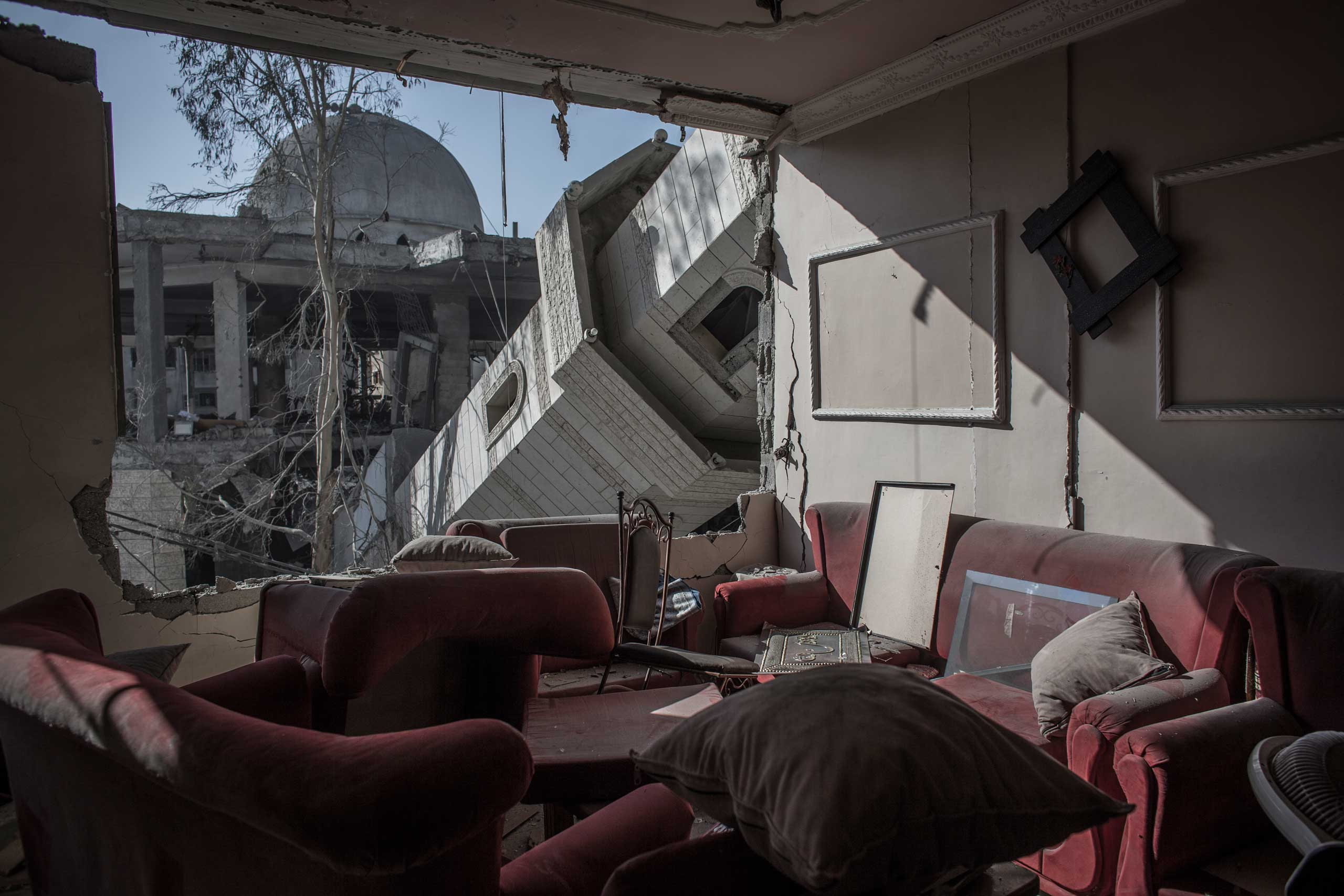 The collapsed minaret of a mosque seen from the destroyed living room of a Palestinian family's home in a building across the street, Gaza City, July 30, 2014.