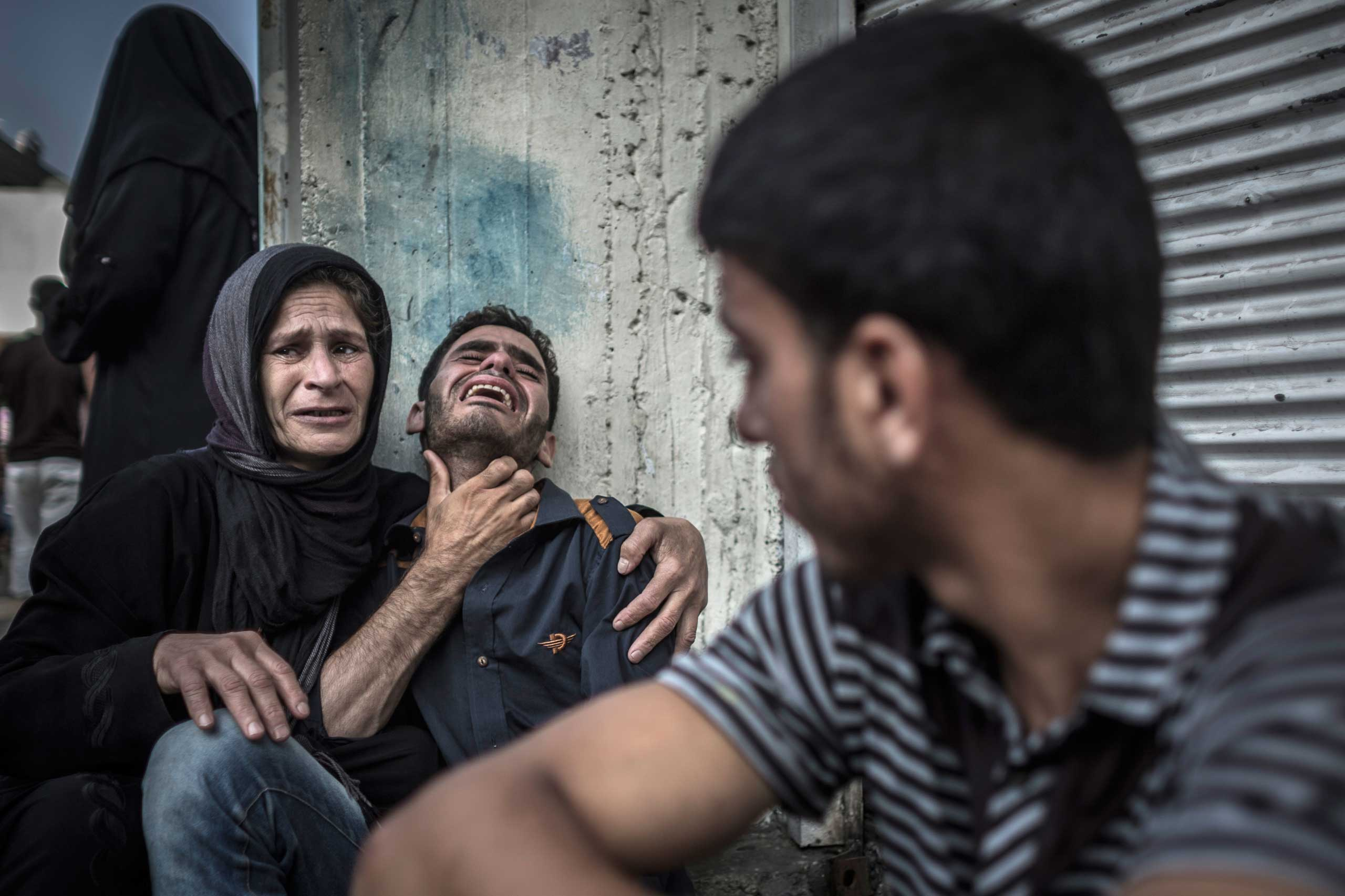 Palestinians mourn the death of a relative who died when a U.N. school used as a shelter for internally displaced people came under Israeli shelling in the Kamal Adwan hospital in Beit Lahiya, northern Gaza Strip, July 30, 2014.
