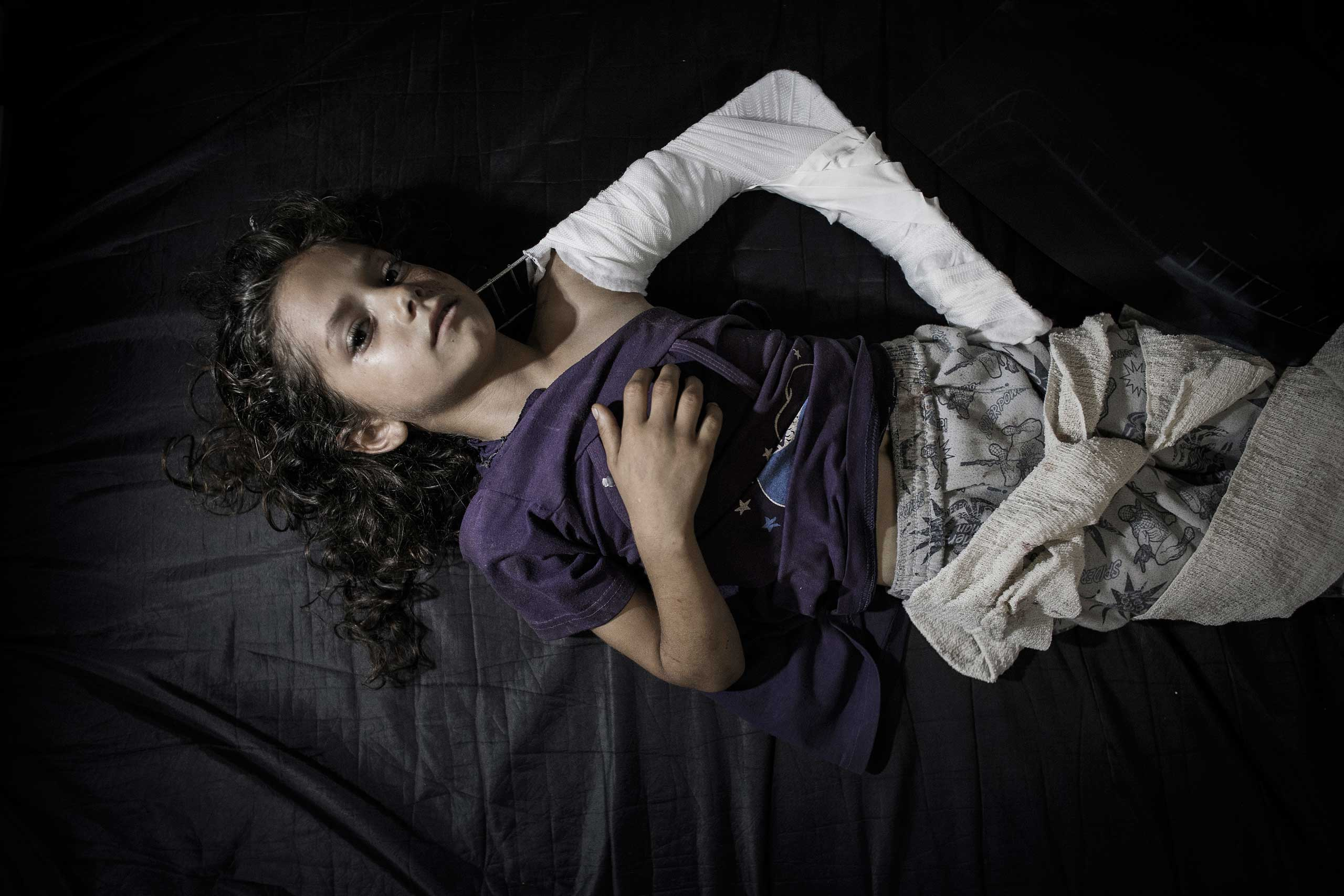 A young Palestinian girl, who was injured when a U.N. school was caught in the crossfire—Israel and Hamas blamed one another—lies on a hospital bed in the emergency room of Kamal Adwan hospital in Beit Lahiya, Gaza Strip, July 24, 2014.