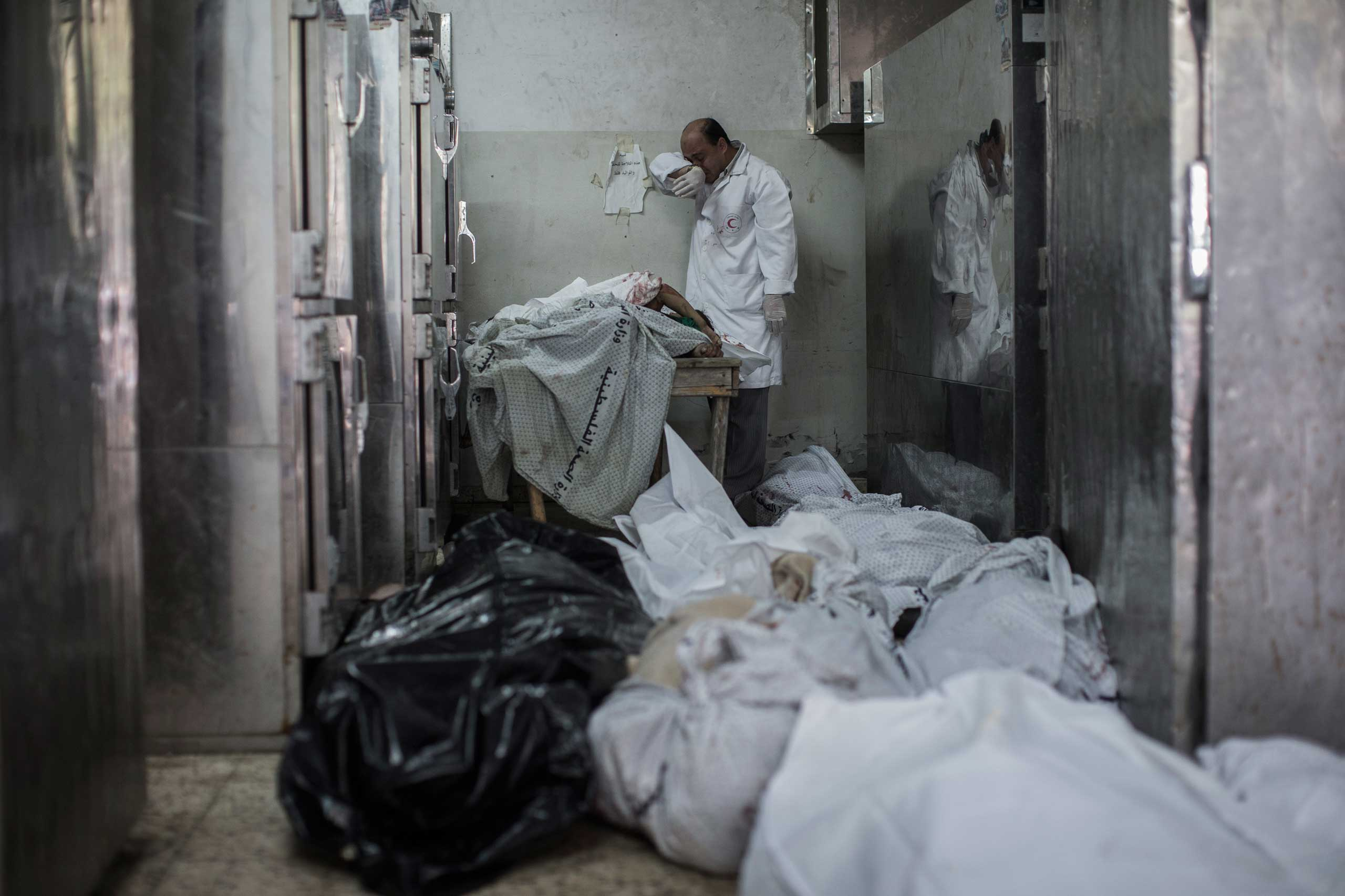 A doctor cries while standing next to a table holding the bodies of four dead children in the overflowing morgue of Shifa Hospital in Gaza City, July 20, 2014.