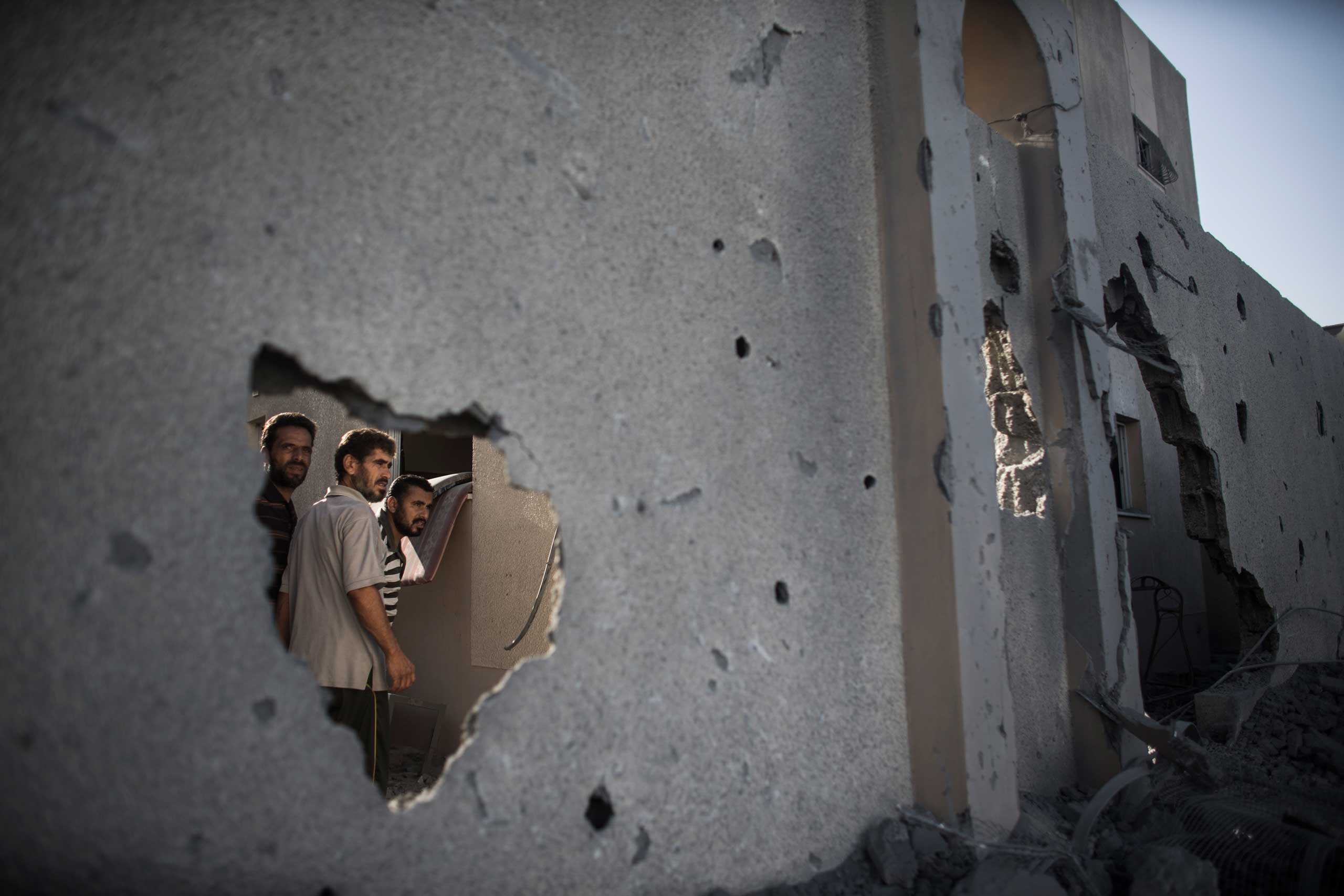 Three Palestinian men look at a destroyed Hamas police station, which was under construction, through a wall of a residential compound destroyed by shrapnel in Rafah, southern Gaza Strip, July 15, 2014.