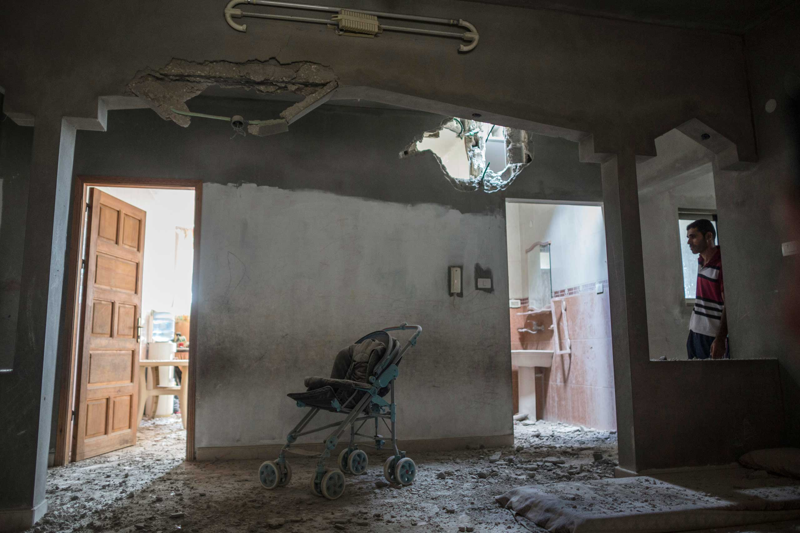 A relative looks at the spot in a Palestinian home where Reza, 1, was killed by shrapnel the night before, Gaza Strip, July 19, 2014.