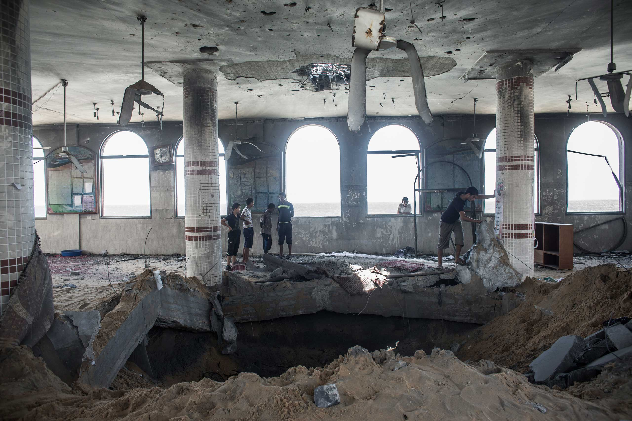 Palestinian boys inspect the damage in a mosque that was destroyed overnight by an Israeli airstrike in Deir Al Balah, central Gaza Strip, July 14, 2014.