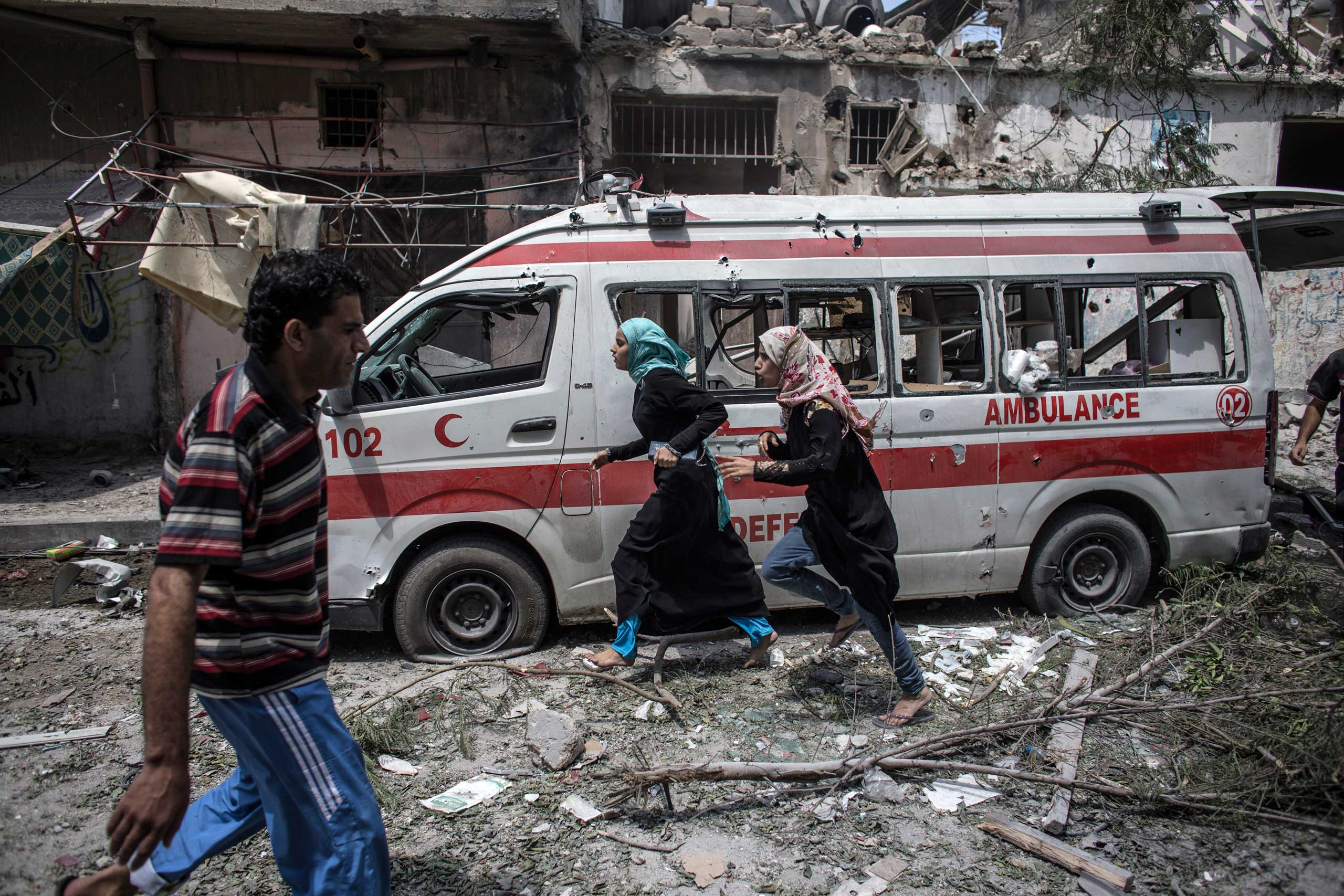 Two Palestinian girls run past a destroyed ambulance as they flee during a brief humanitarian cease-fire requested by local rescue forces to retrieve dead and wounded from Shejaiya, in east Gaza City, July 20, 2014.