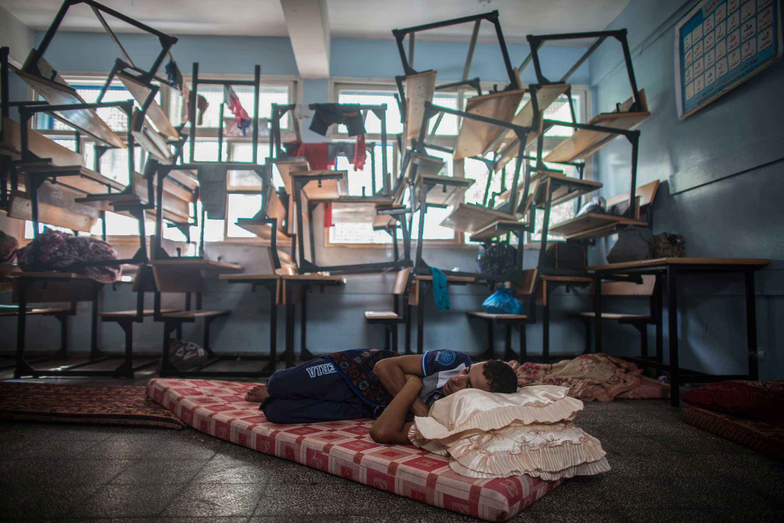 A man who fled from Beit Lahiya, in the northern Gaza Strip, sleeps in a U.N. school that was transformed into a shelter for displaced persons, Gaza City, July 13, 2014.