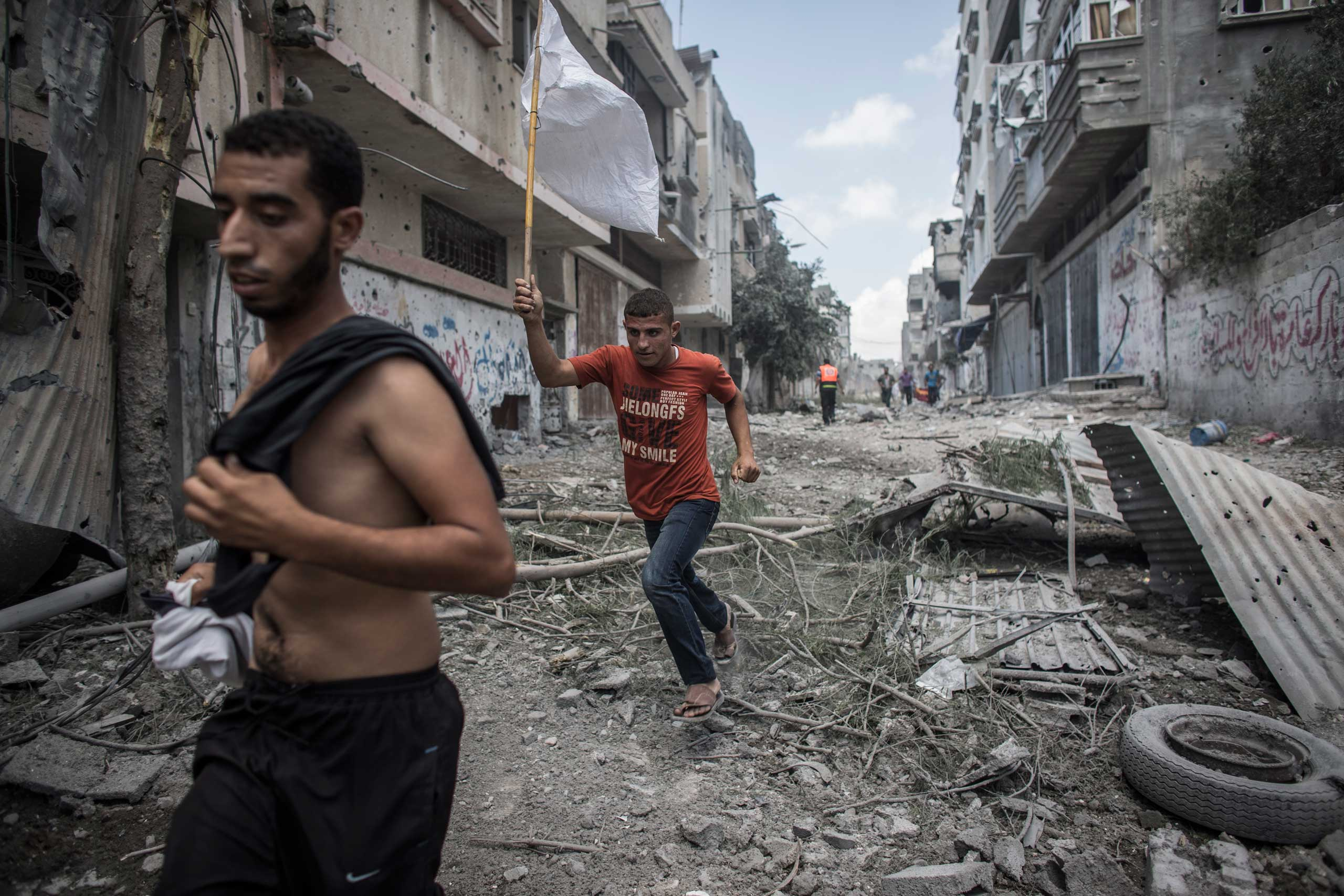 Two Palestinian men carry a white flag as they flee their homes during a brief humanitarian cease-fire in Shejaiya, in east Gaza City, July 20, 2014.