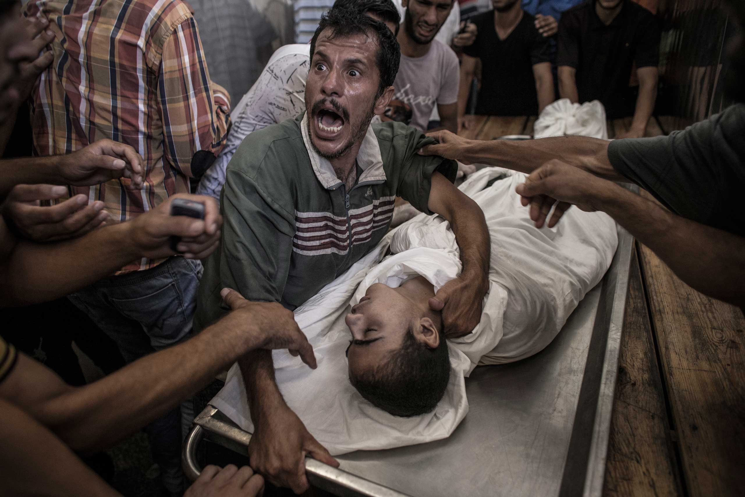 A Palestinian man cries over the body of his son, who died when medics say the U.N. school sheltering displaced persons came under fire, in the Kamal Adwan hospital in Beit Lahiya, Gaza Strip, July 24, 2014.