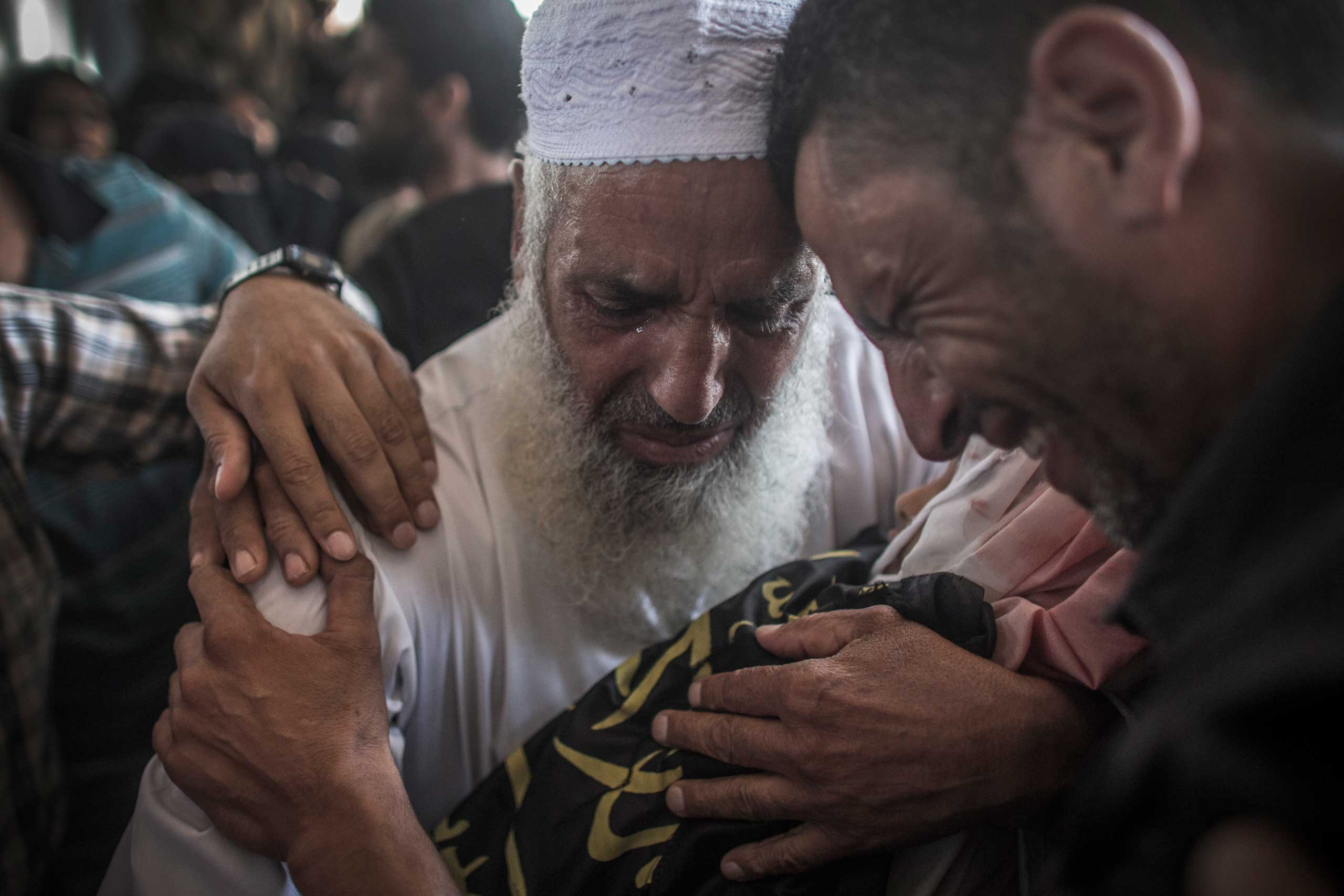 Relatives cry as they hold the body of Sara, 4, during her funeral outside Rafah, southern Gaza Strip, July 15, 2014.