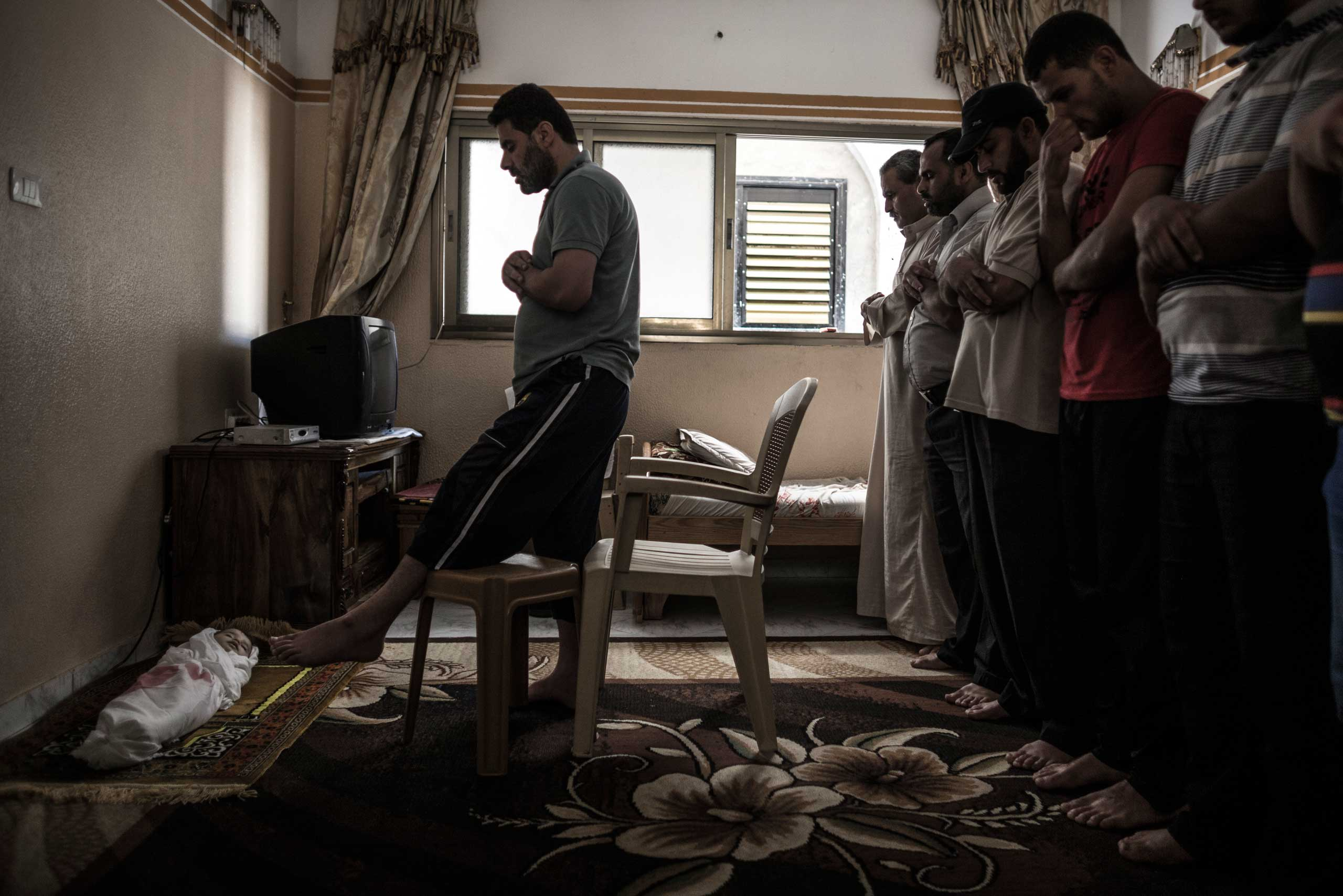Relatives pray in front of the body of Razel, 1, during her funeral in Khan Younis, central Gaza Strip, July 18, 2014.