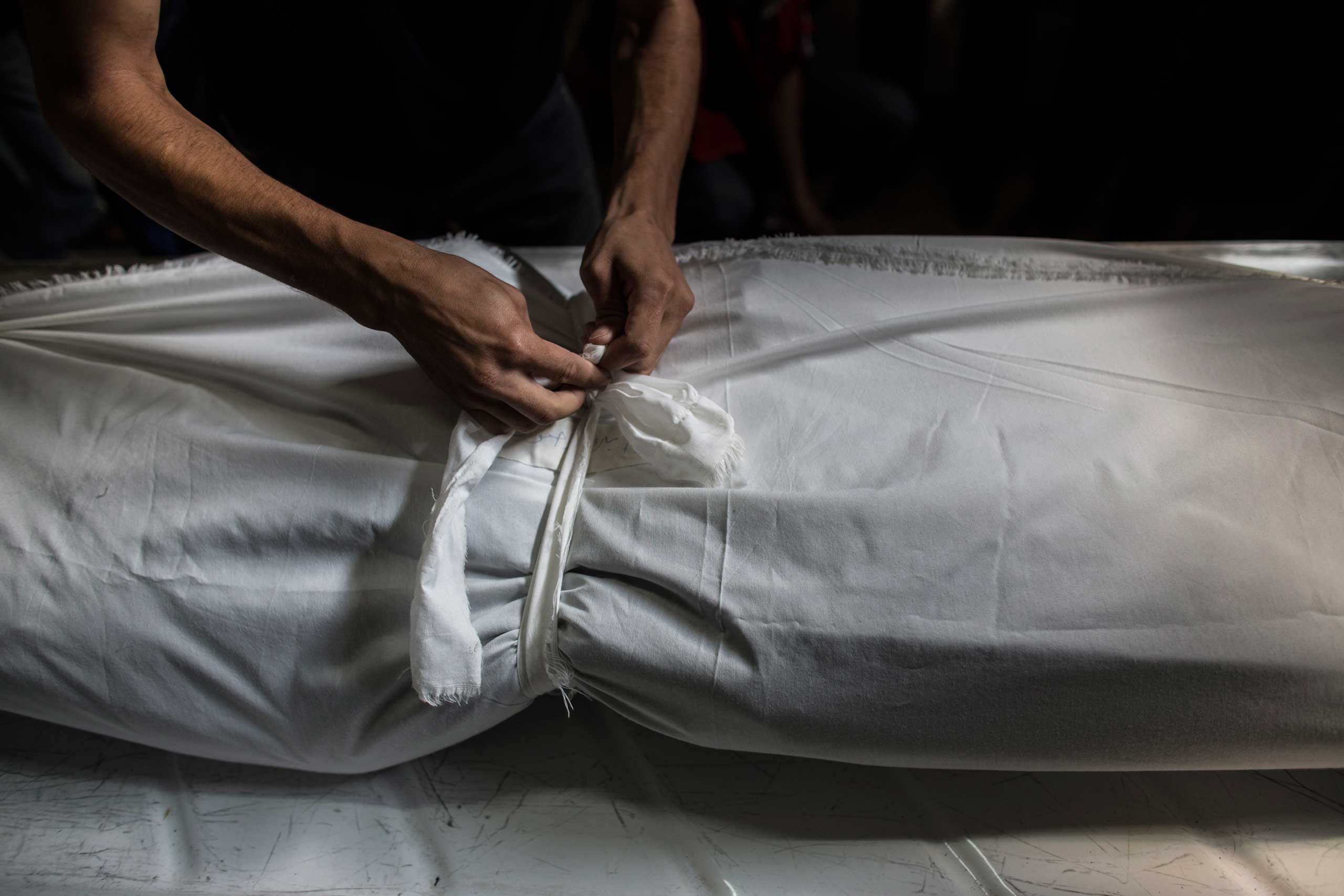 A Palestinian mortician ties a knot around a sheet covering the body of a dead Palestinian man in a morgue in Khan Younis, central Gaza City, July 18, 2014.