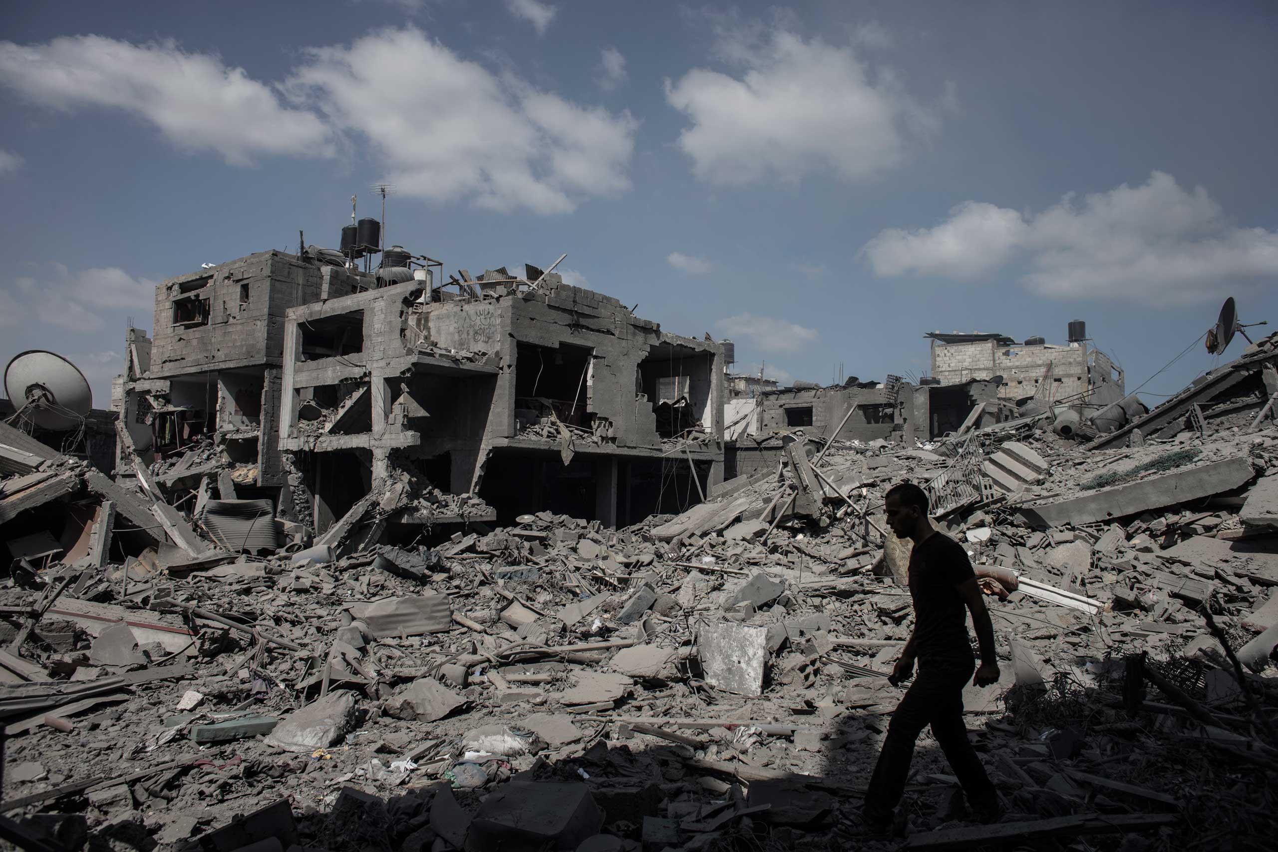 A Palestinian man walks past destroyed houses in Beit Hanoun, northern Gaza Strip, July 16, 2014.