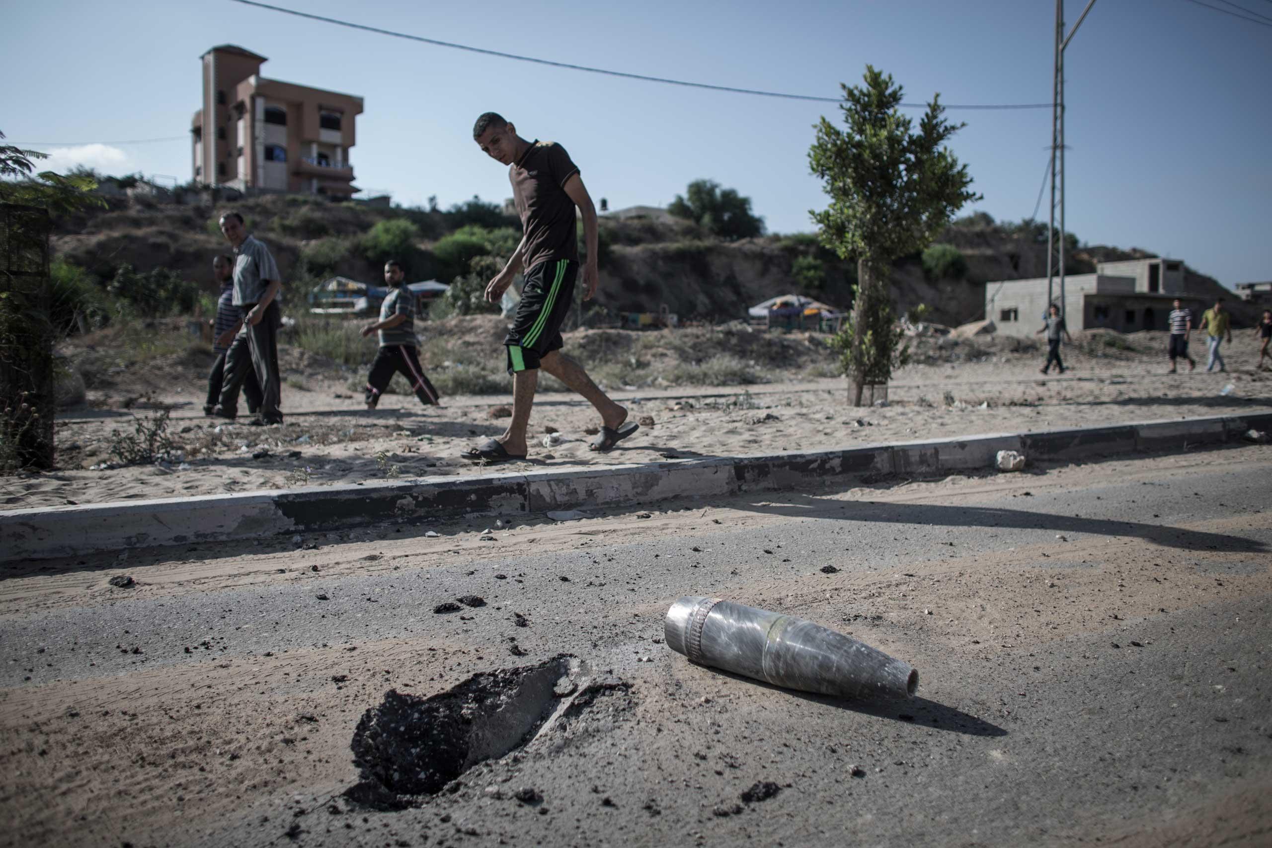 Palestinians walk past an unexploded Israeli shell outside Beit Hanoun, northern Gaza Strip, July 26, 2014.