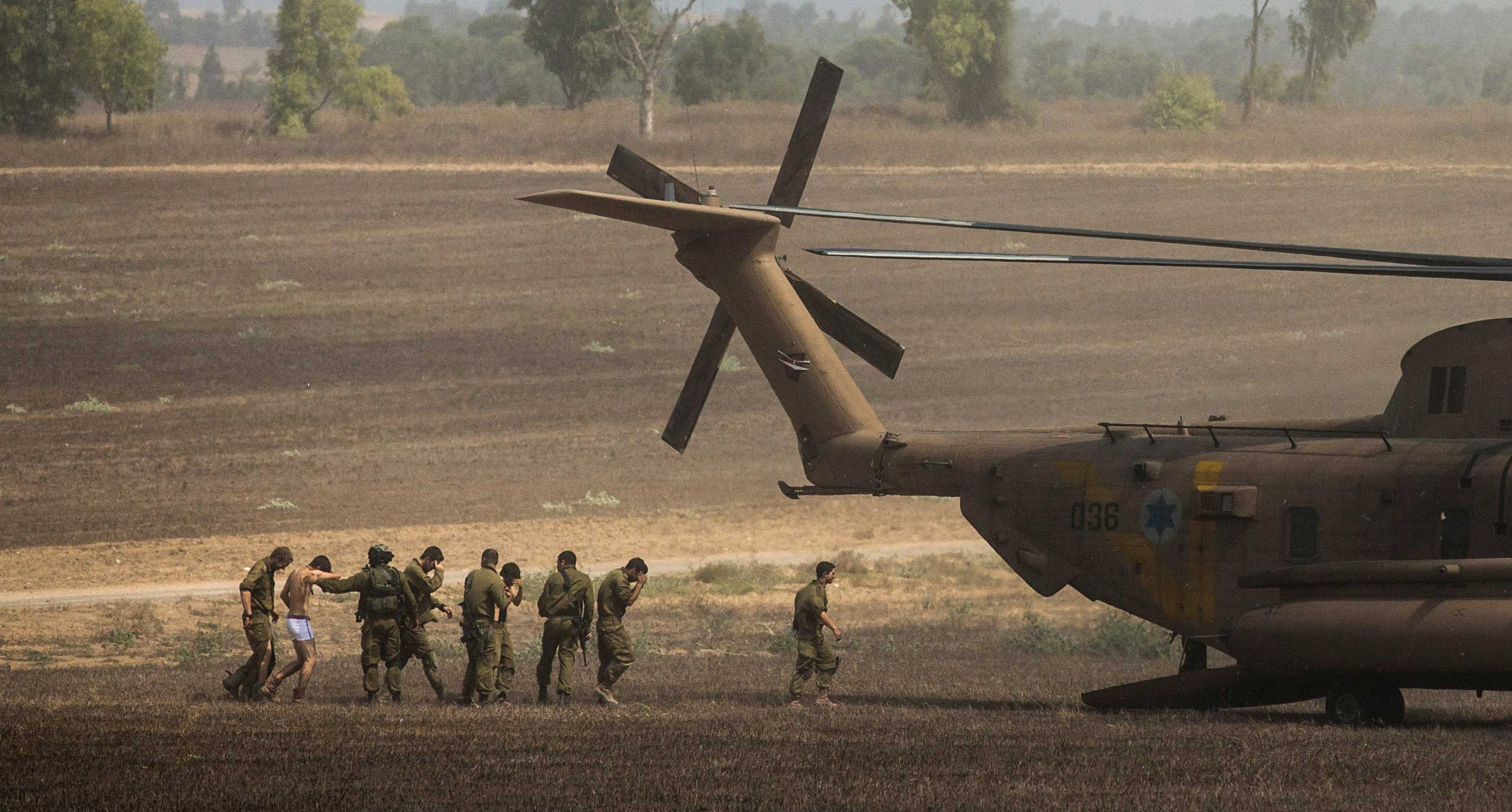 Wounded Israeli soldiers are brought to a helicopter, near Kfar Aza, Israel, on July 23, 2014.