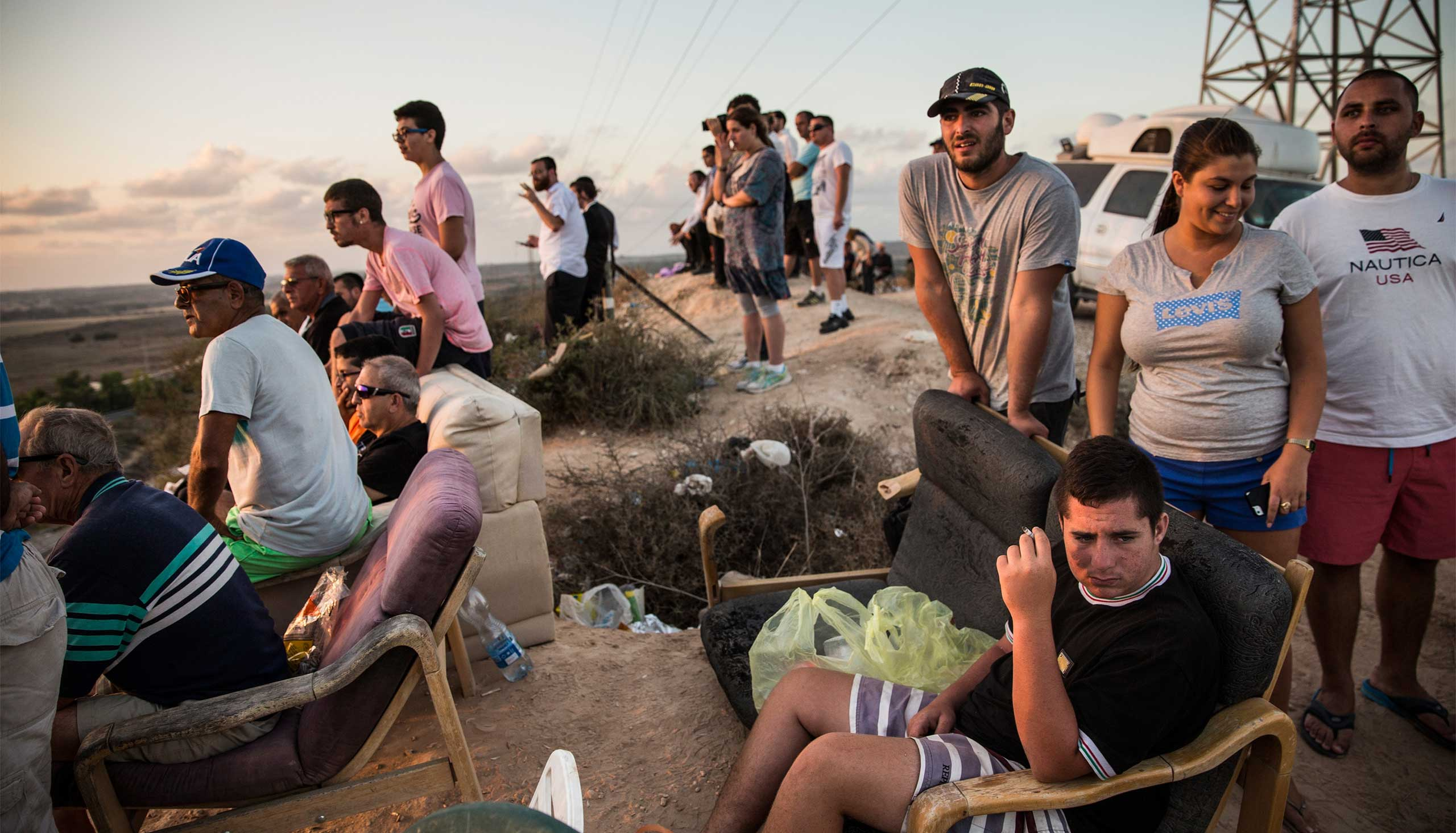 Israelis look for outgoing rocket fire from Gaza and wait for Israeli airstrikes from a hill overlooking the Gaza Strip in Sderot, Israel, July 14, 2014.
