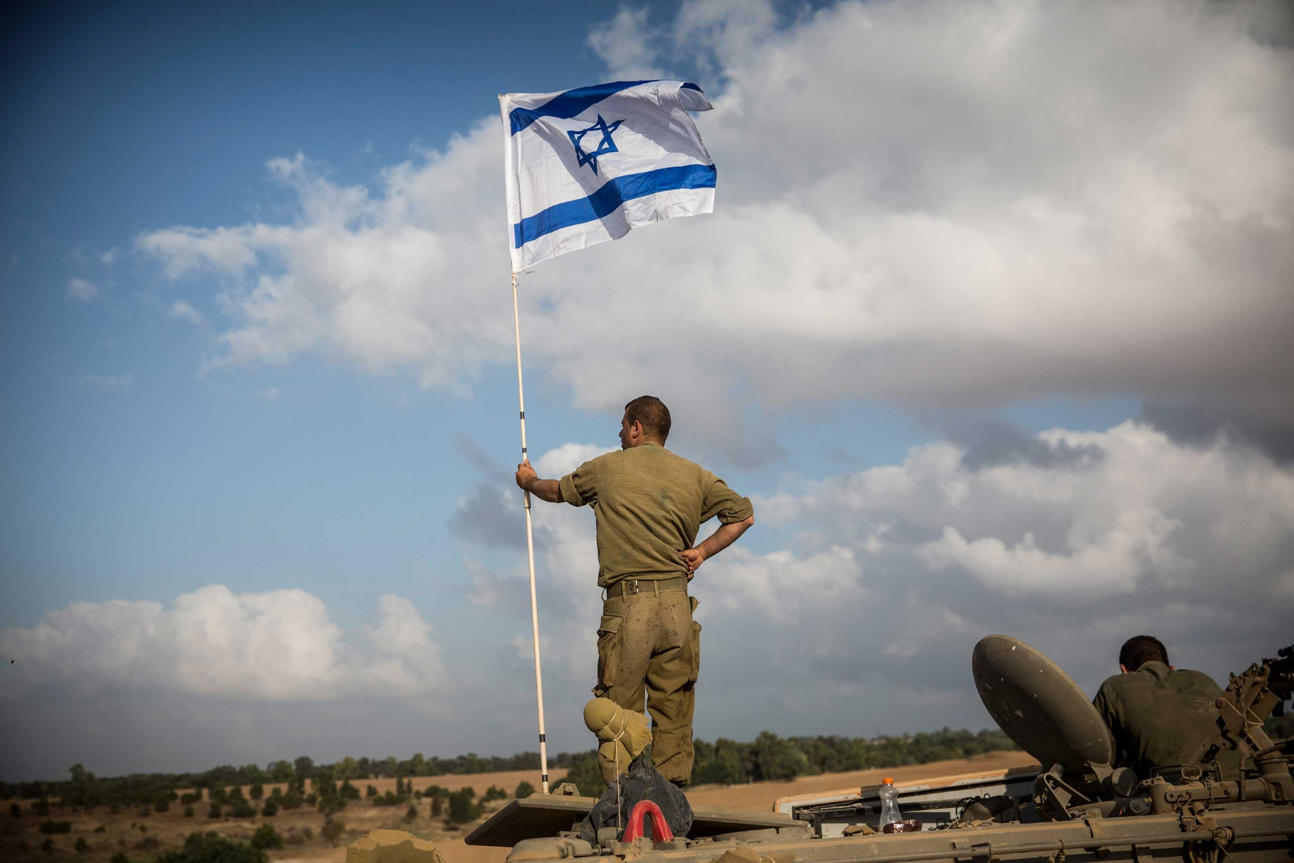 An Israeli soldier stands on top of an armored personnel carrier close to the Israel-Gaza border near Sderot, Israel, July 15, 2014.