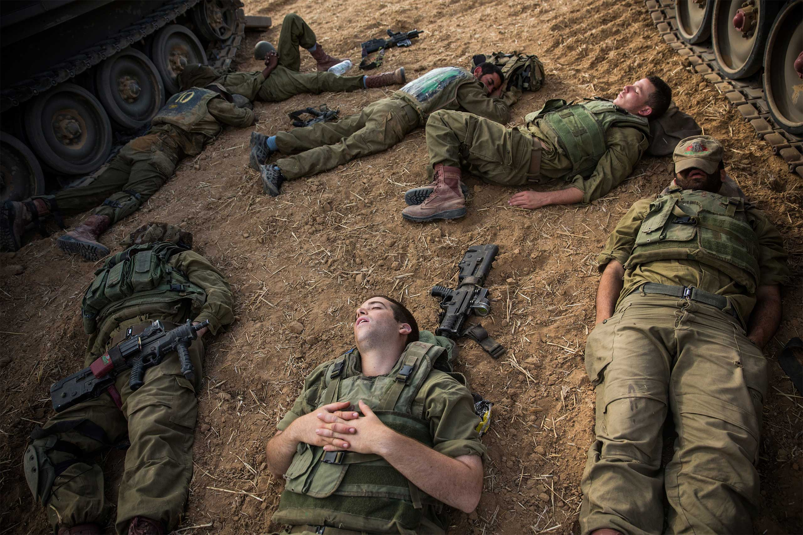 Israeli soldiers sleep next to armored personnel carriers close to the Israel-Gaza border near Sderot, Israel, July 15, 2014.
