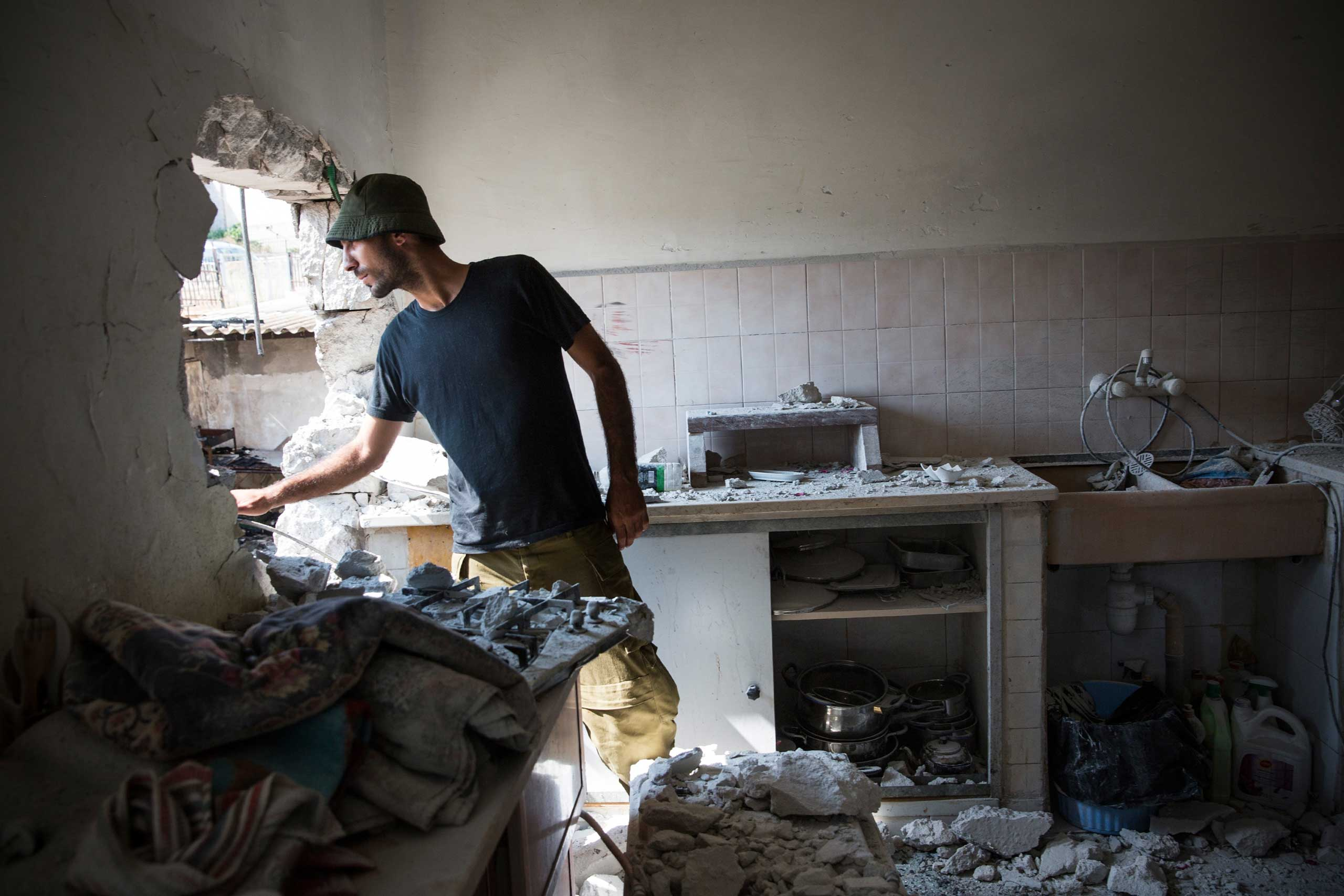 An Israeli soldier inspects a home allegedly hit by a Hamas rocket in Sderot, Israel, July 21, 2014.
