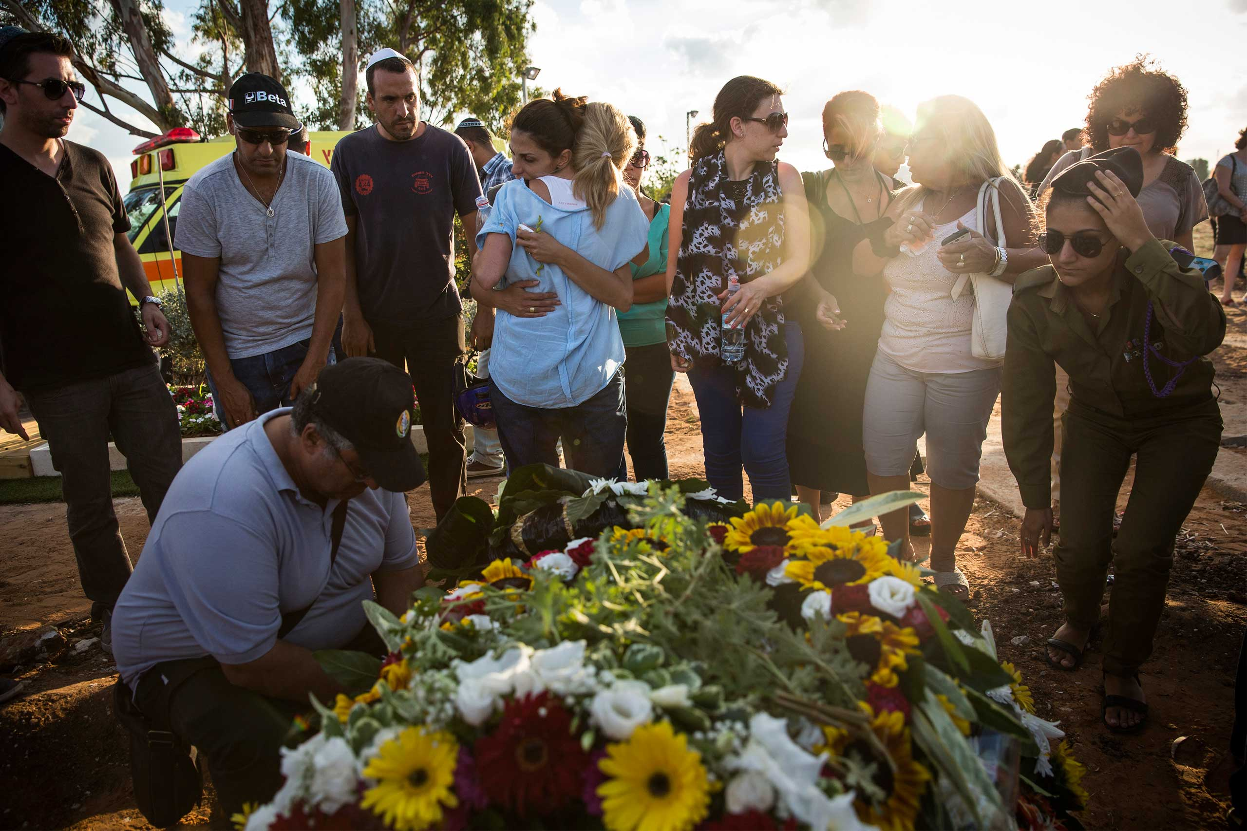 People mourn during the funeral of Dror Khenin at a cemetery in Yahud Monoson, Israel, July 16, 2014.